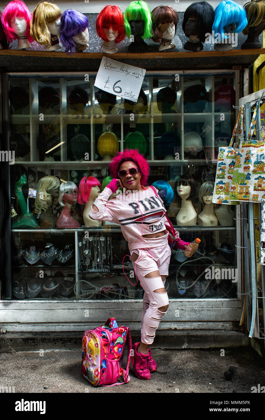 Lady dressed in pink wearing a pink wig poses in front of a wig shop in Brixton Village London SW2 Stock Photo