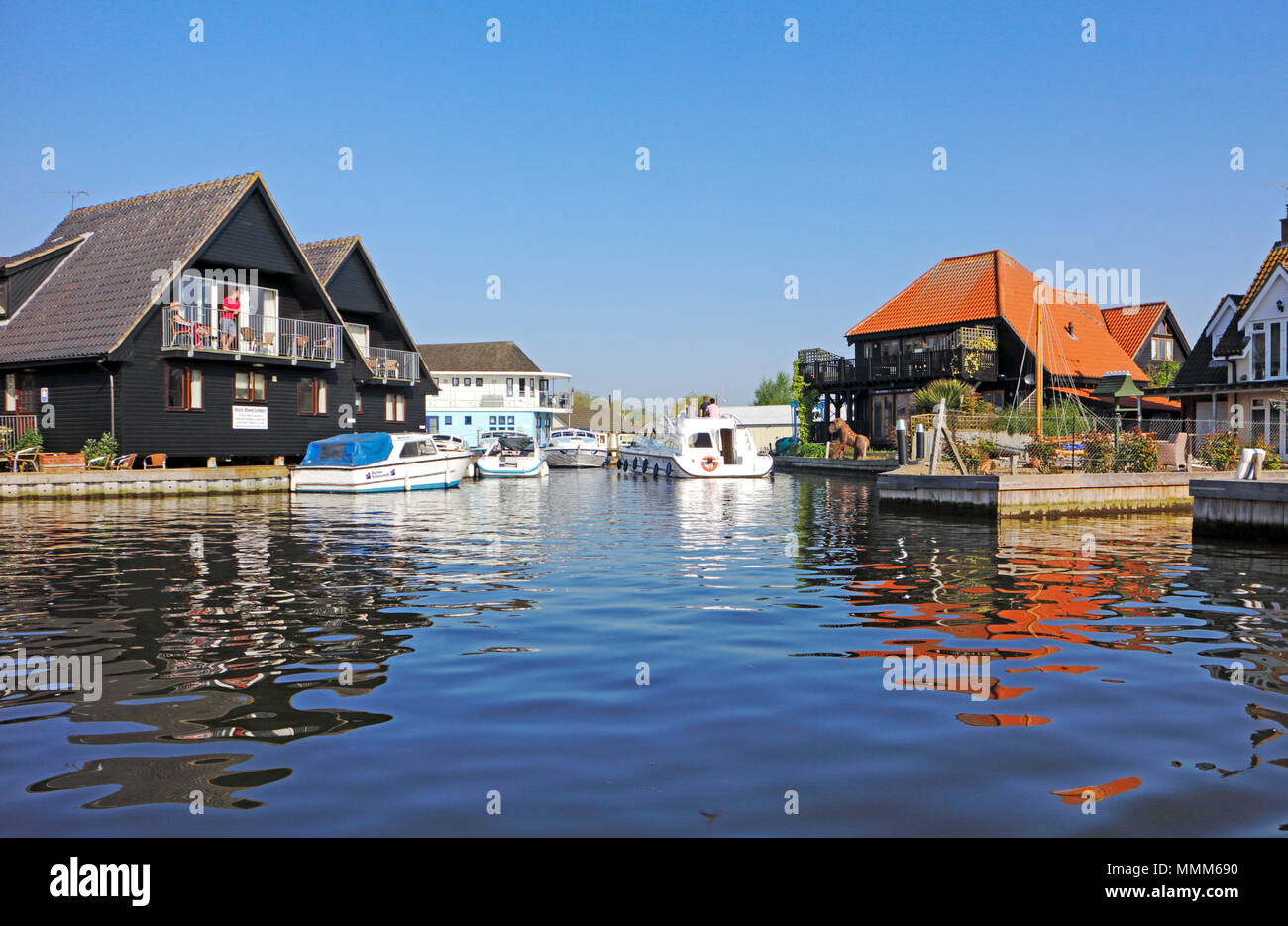 Riverside properties and boat dykes by the River Bure on the Norfolk Broads at Wroxham, Norfolk, England, United Kingdom, Europe. Stock Photo