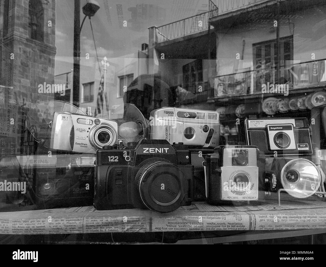 Nicosia, Cyprus - April 26, 2018: An assortment of classic vintage film cameras and flash units displayed in an antique shop window - Stock Image