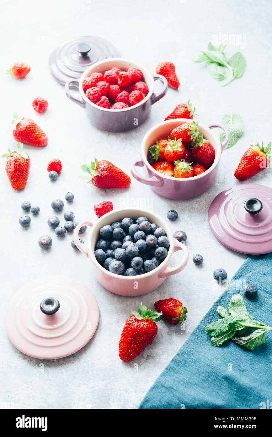 Summer fruit background, top view of berries , smoothie ingredient, inside ceramic colored cocotte, blueberries, strawberries, raspberries, flat lay - Stock Image