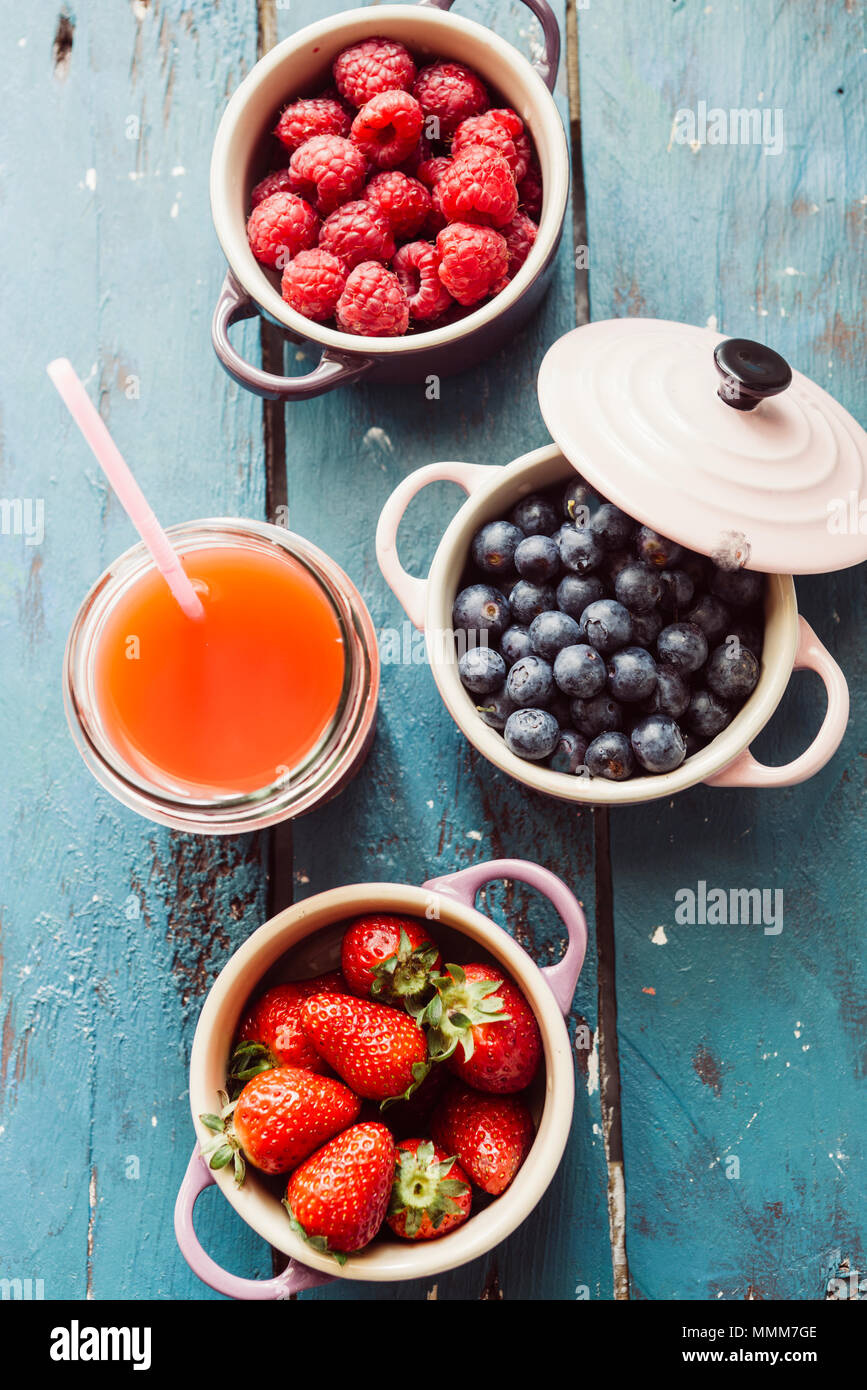 Summer fruit background, top view of berries inside ceramic colored cocotte, blueberries, strawberries, raspberries, flat lay, blue table. Detox and h - Stock Image
