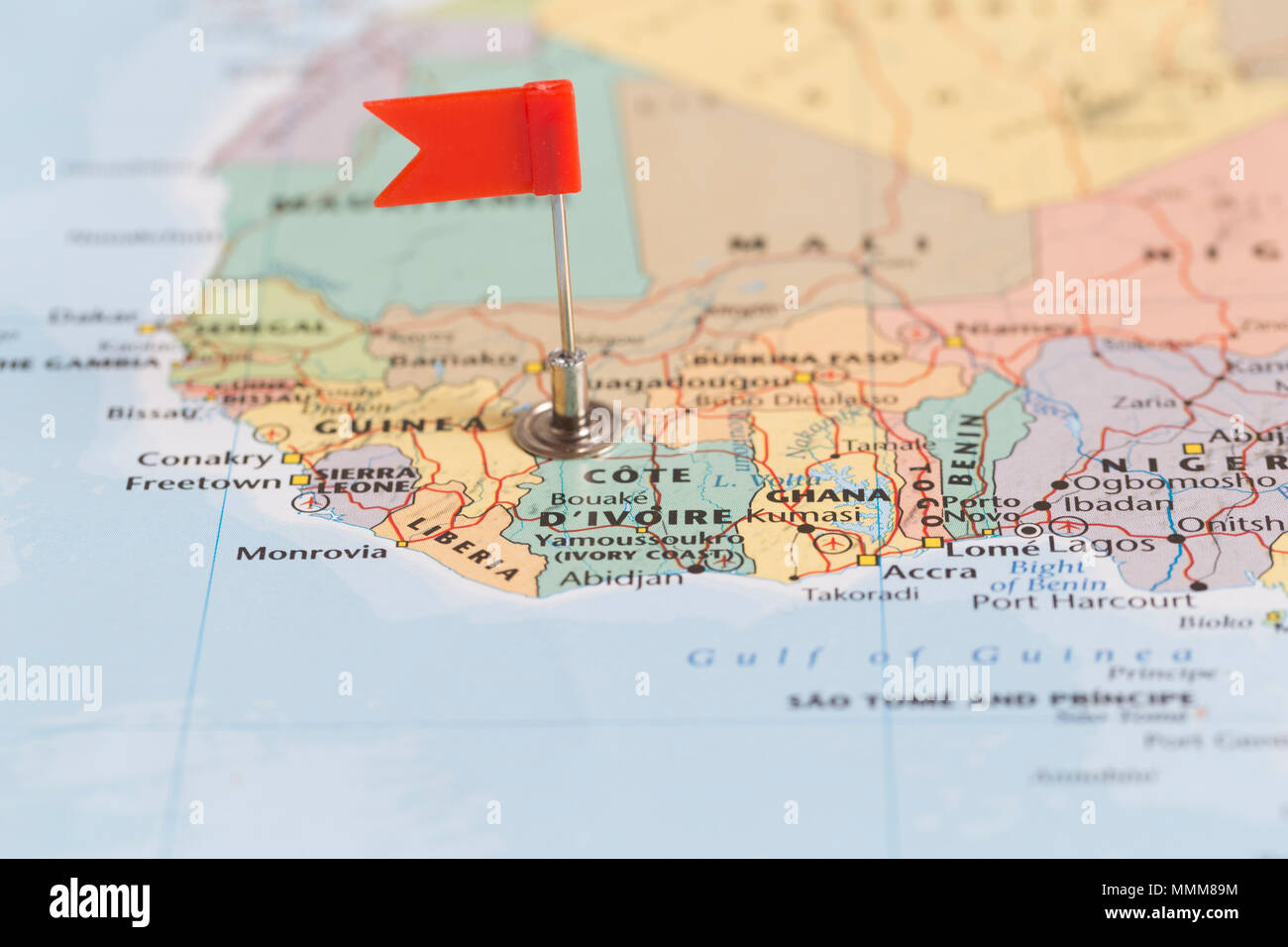 Small red flag marking the African country of  Cote D'Ivoire on a world map. - Stock Image