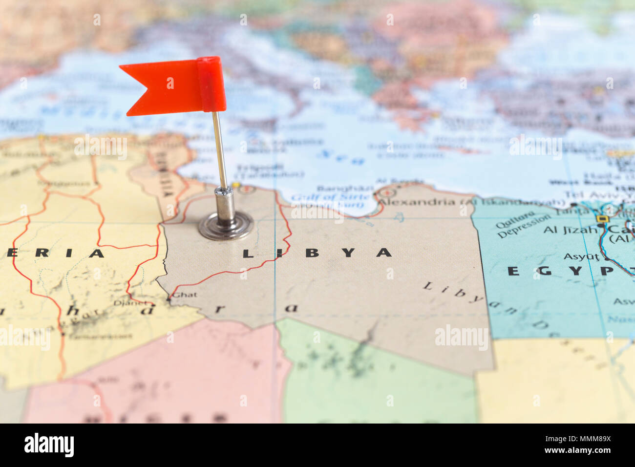Libya On A World Map.Small Red Flag Marking The African Country Of Libya On A World Map