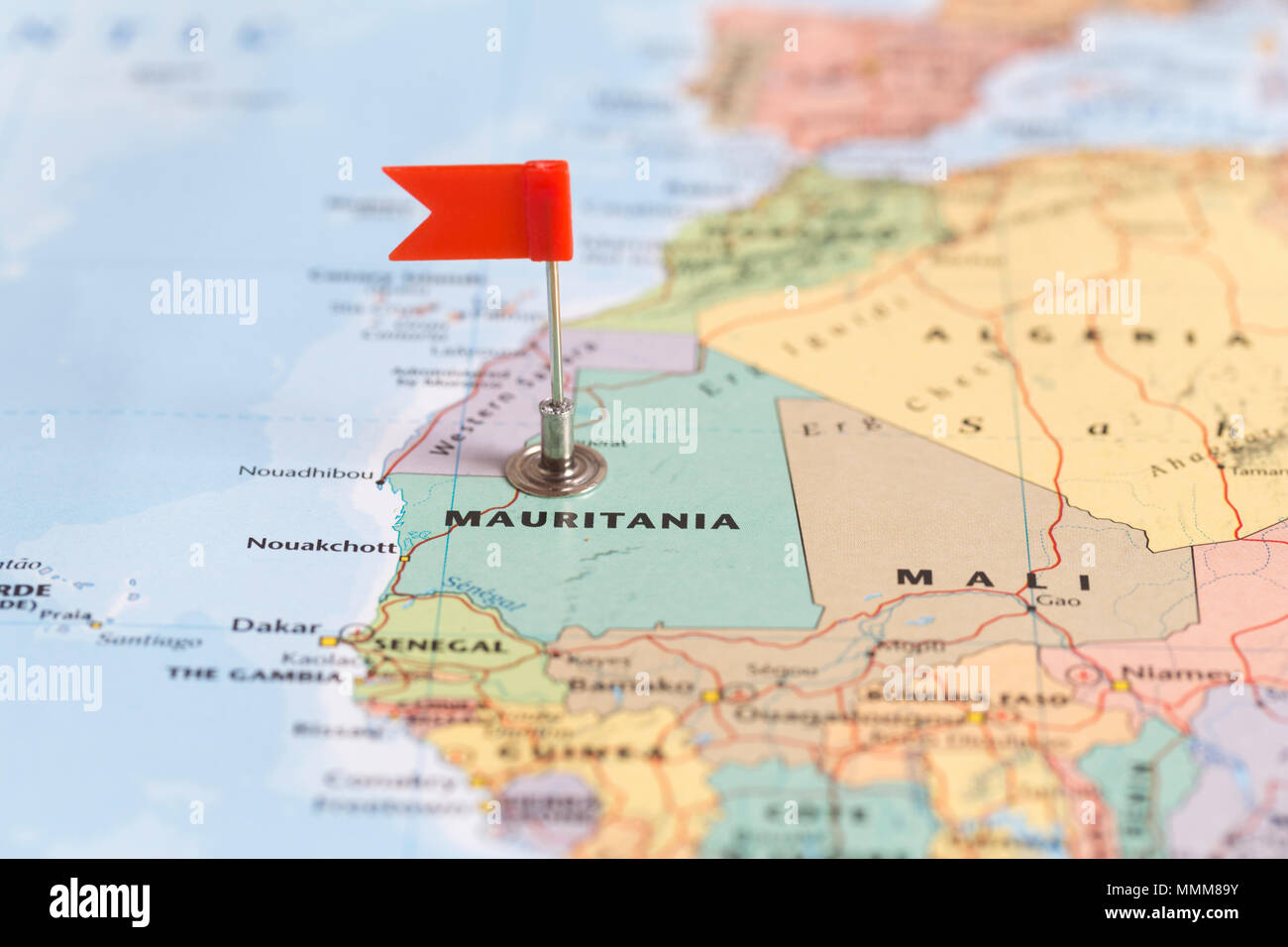 Small red flag marking the African country of  Mauritania on a world map. - Stock Image