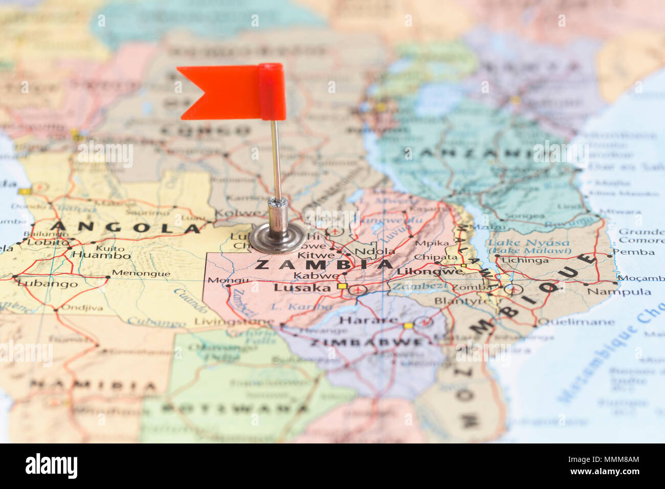 Small red flag marking the African country of Zambia on a world map ...