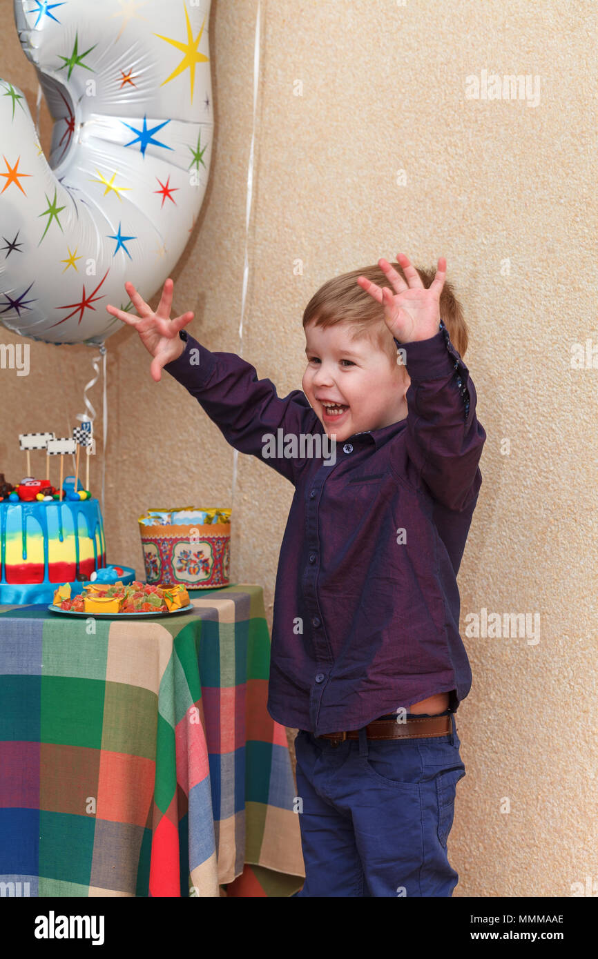 A happy little boy is very happy with gifts and a sweet cake on his birthday - Stock Image