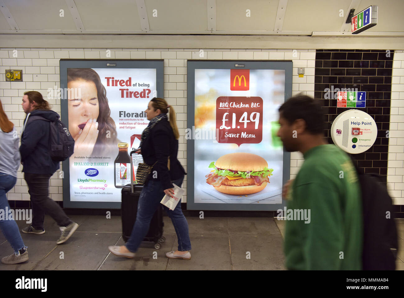 People walk past advertising hoardings promoting McDonalds BBQ Chicken burger in the Notting Hill underground station in central London.  Junk food ad - Stock Image