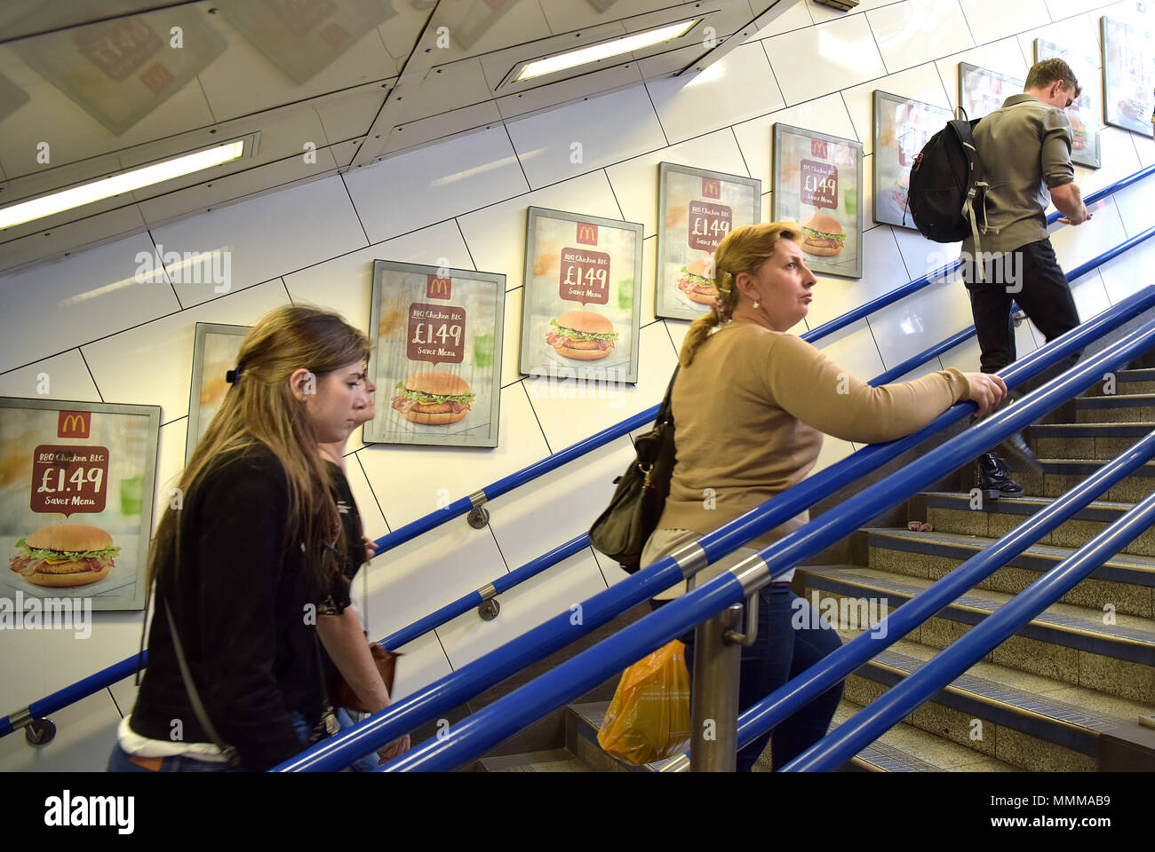 People walk past advertising hoardings promoting McDonalds BBQ Chicken burger in the Oxford Circus underground station in central London.  Junk food a - Stock Image