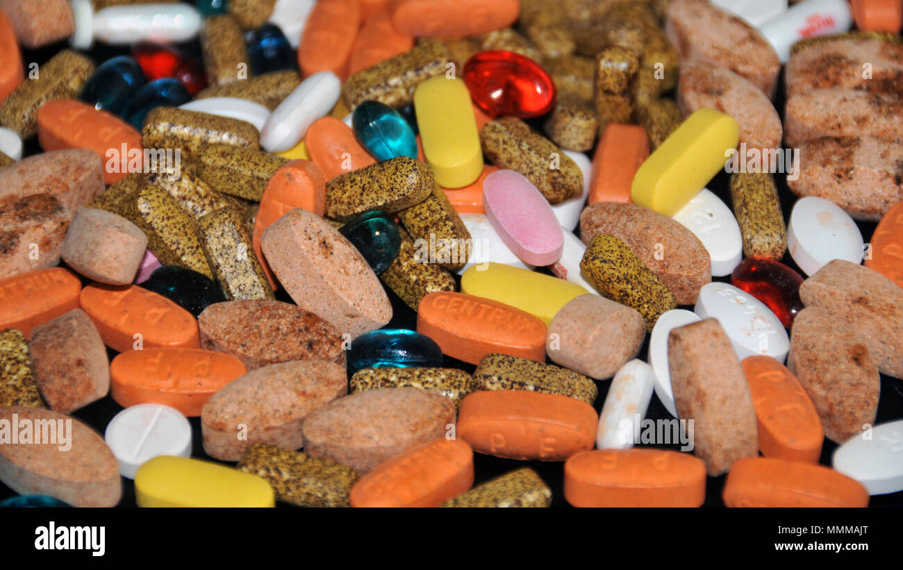 A mix of pills containing prescribed medicines and dietary supplements - Stock Image