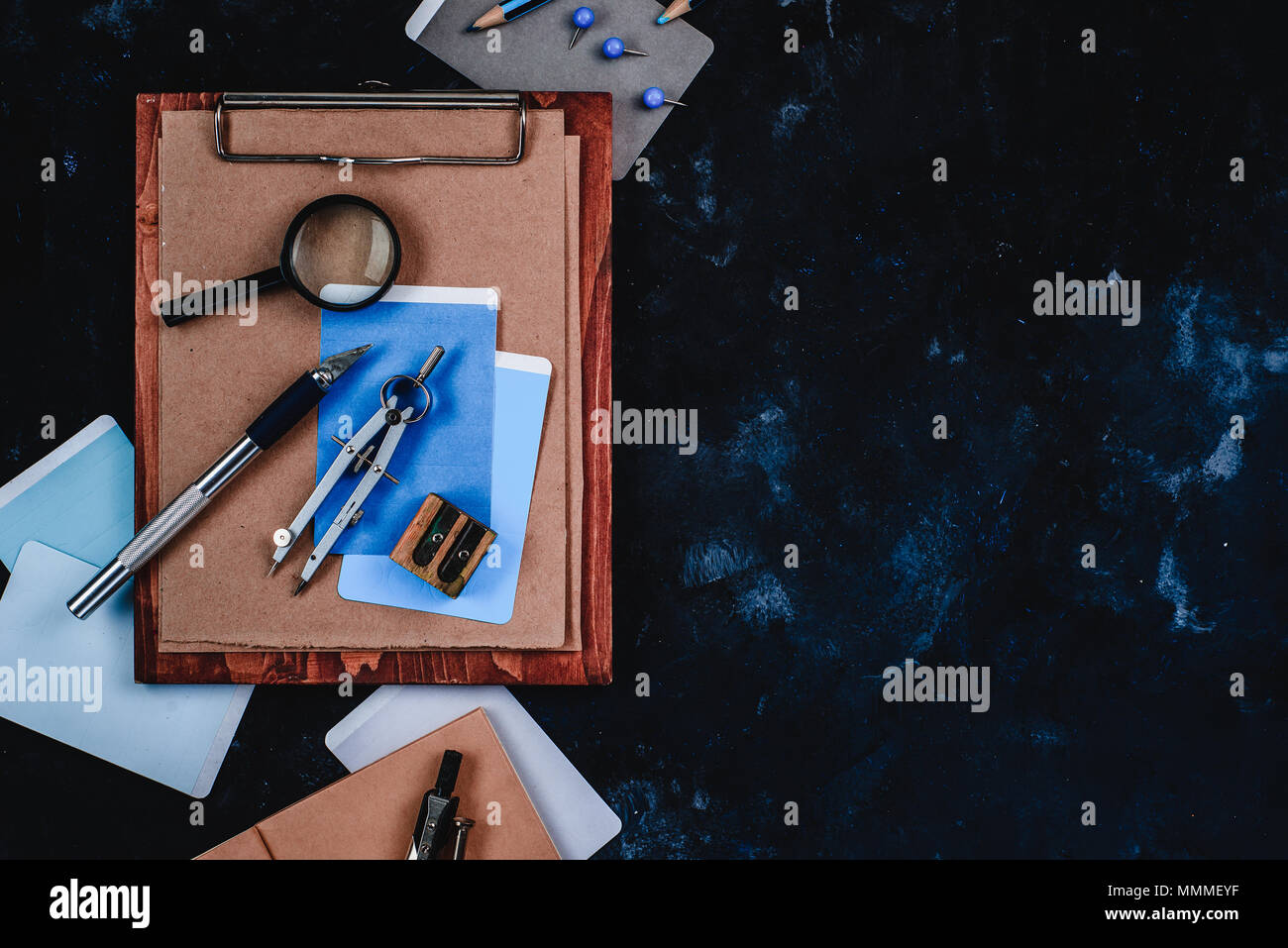 Clipboard with craft paper and sketches on a designer workplace. Sketches, compasses, rulers, clipboards and pencils in an architect or interior desig - Stock Image