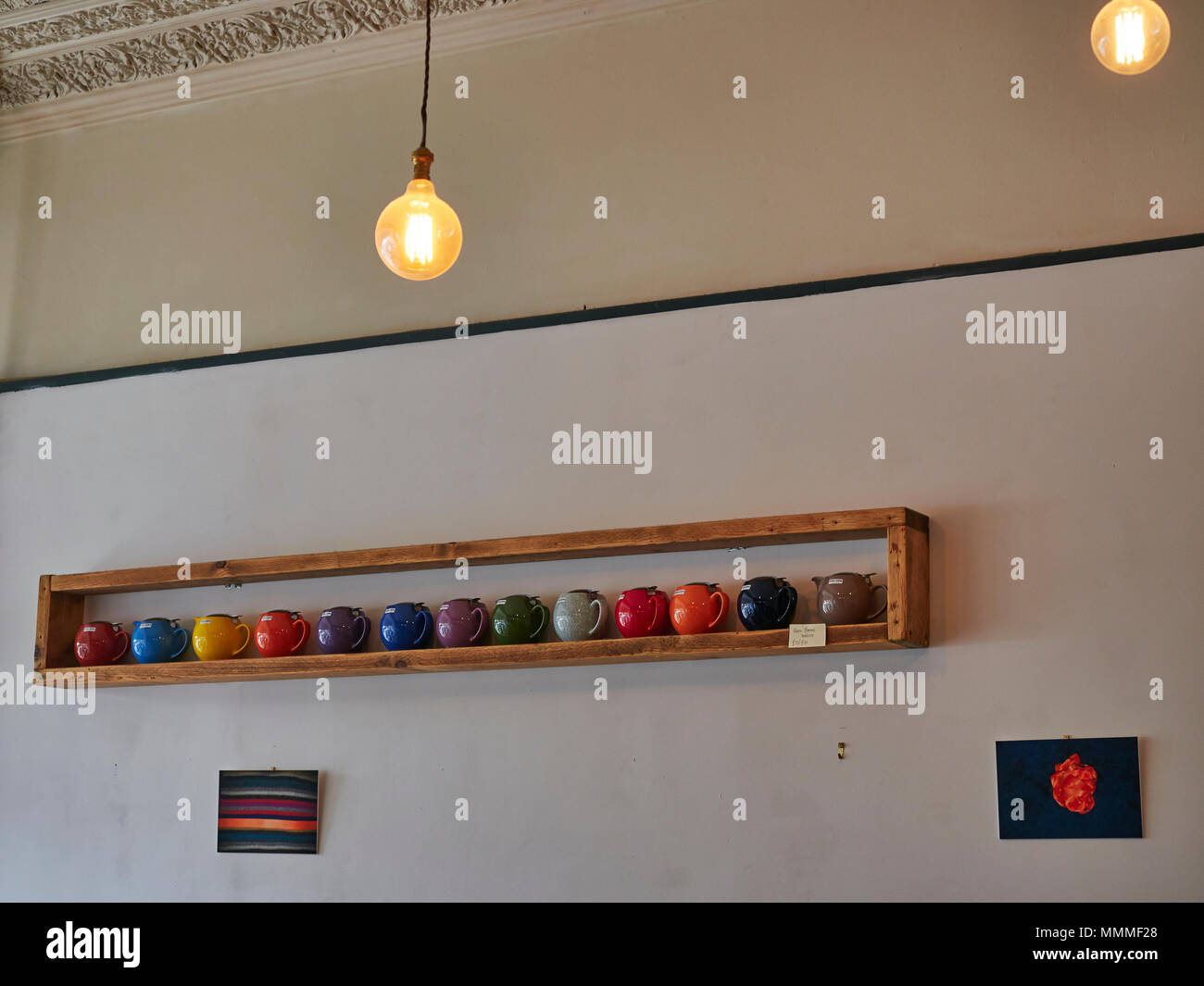 A row of brightly coloured Teapots for Sale on a rustic wooden shelf in the Red Kite Cafe in Edinburgh, Scotland. - Stock Image