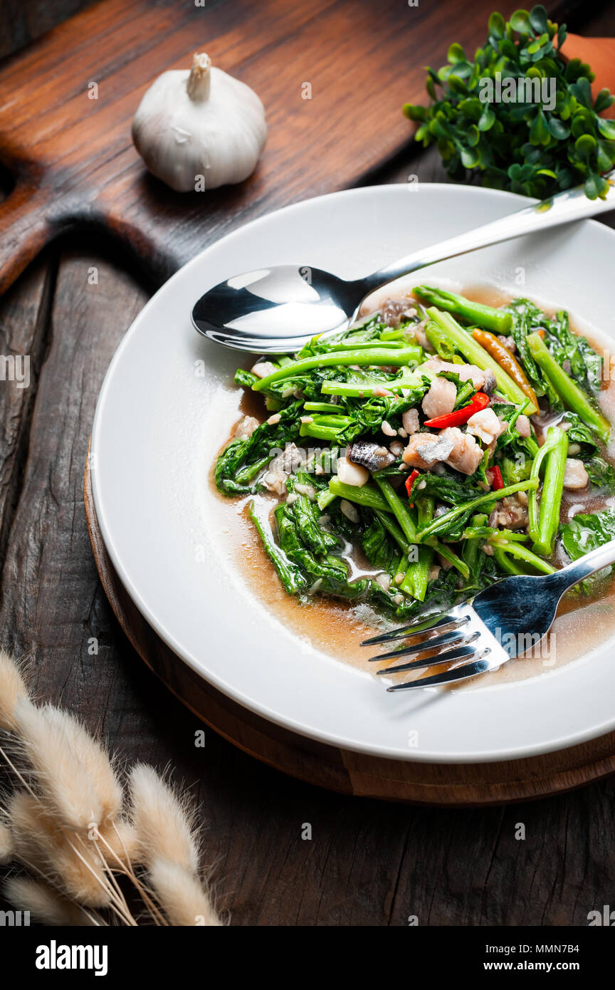 Thai food : Stir-fried kale with sun-dried salted fish on wooden table - Stock Image