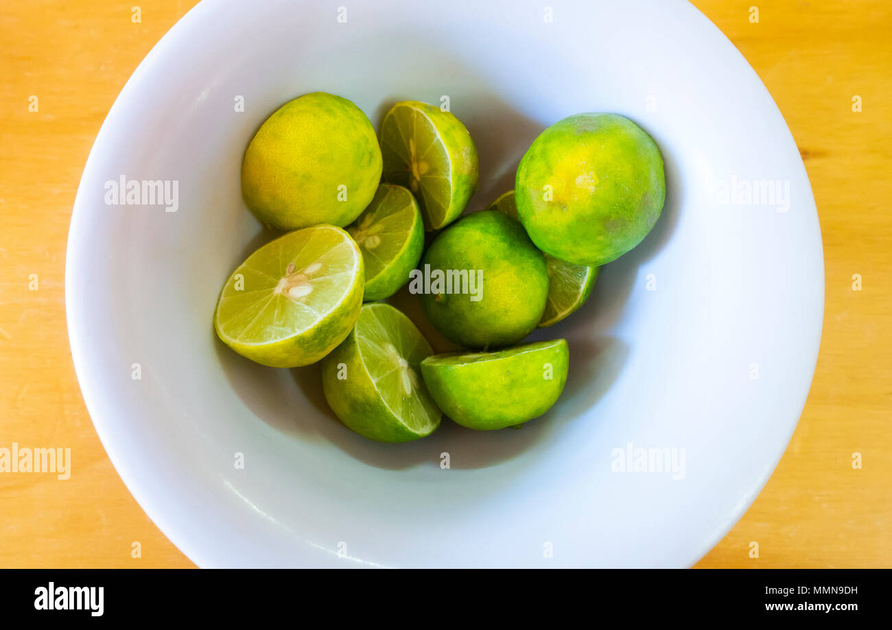 A bowl of halved fresh green lemons - Stock Image