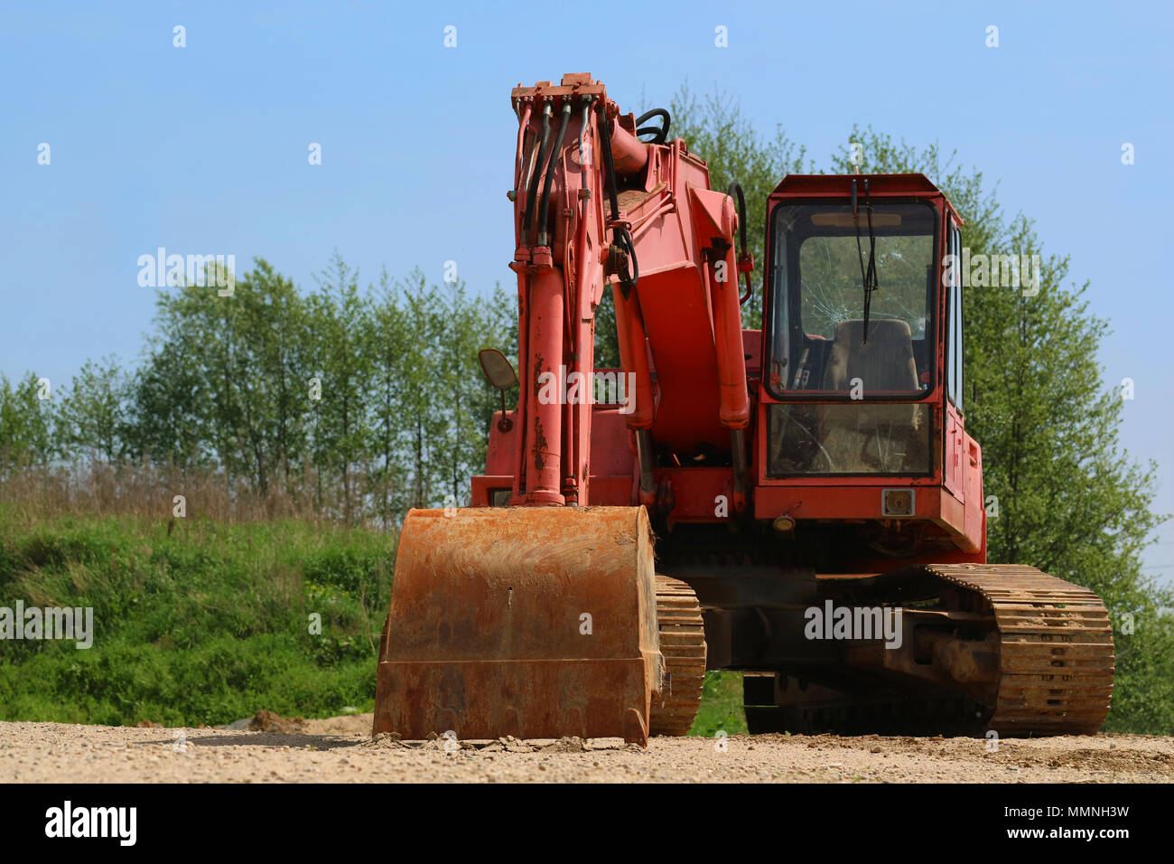 Old rusty excavator with broken window on sandy ground - Stock Image