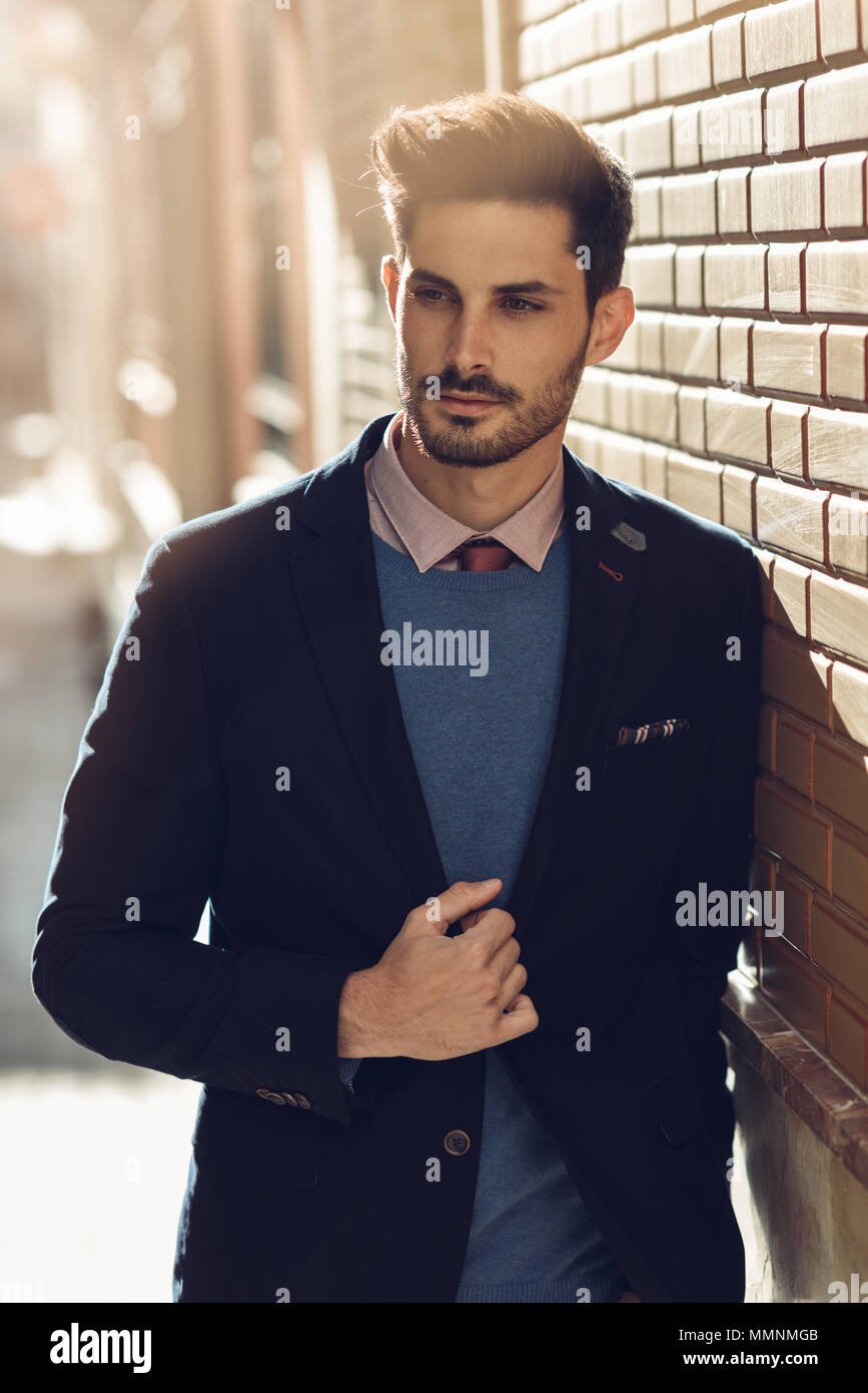 attractive man in the street wearing british elegant suit. young