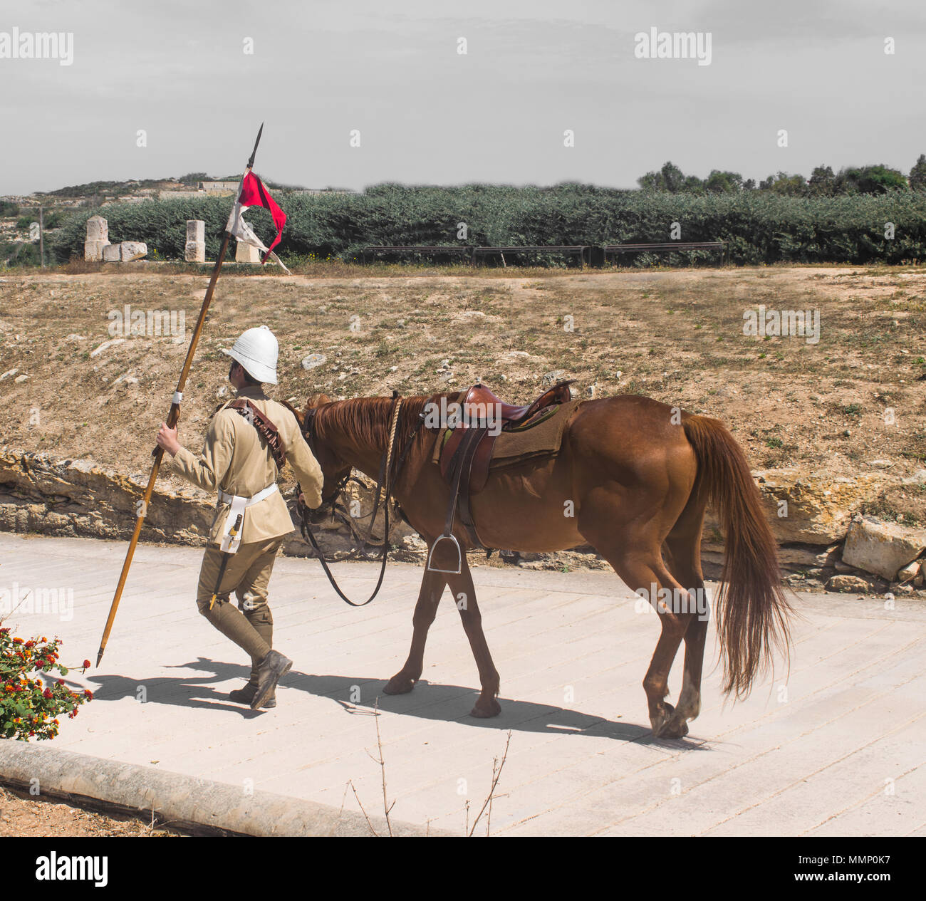 A soldier walking along with his horse symbolizing the cavalry of the Victorian Era. - Stock Image