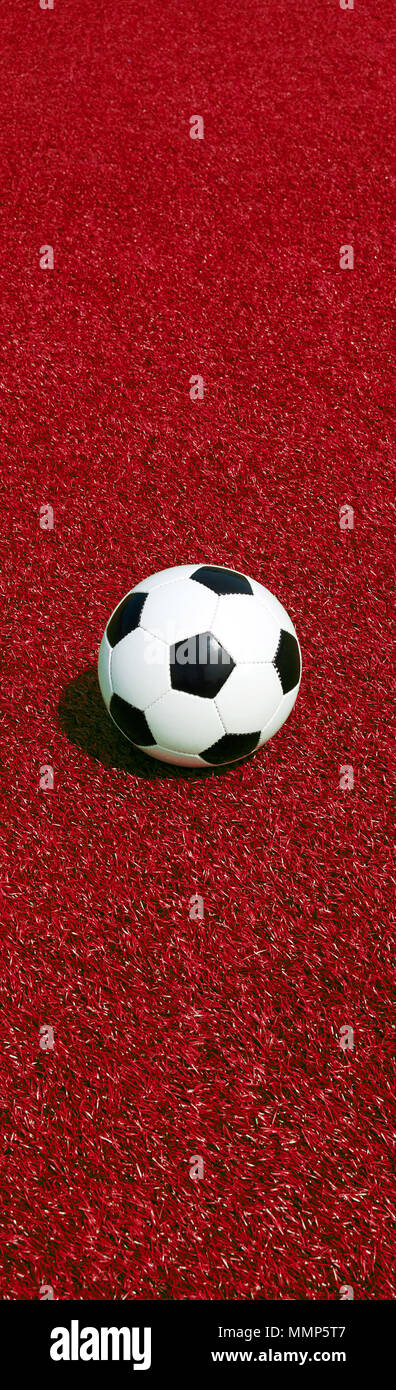 soccer ball on red ground, panoramic format, portrait format on, football banner - Stock Image
