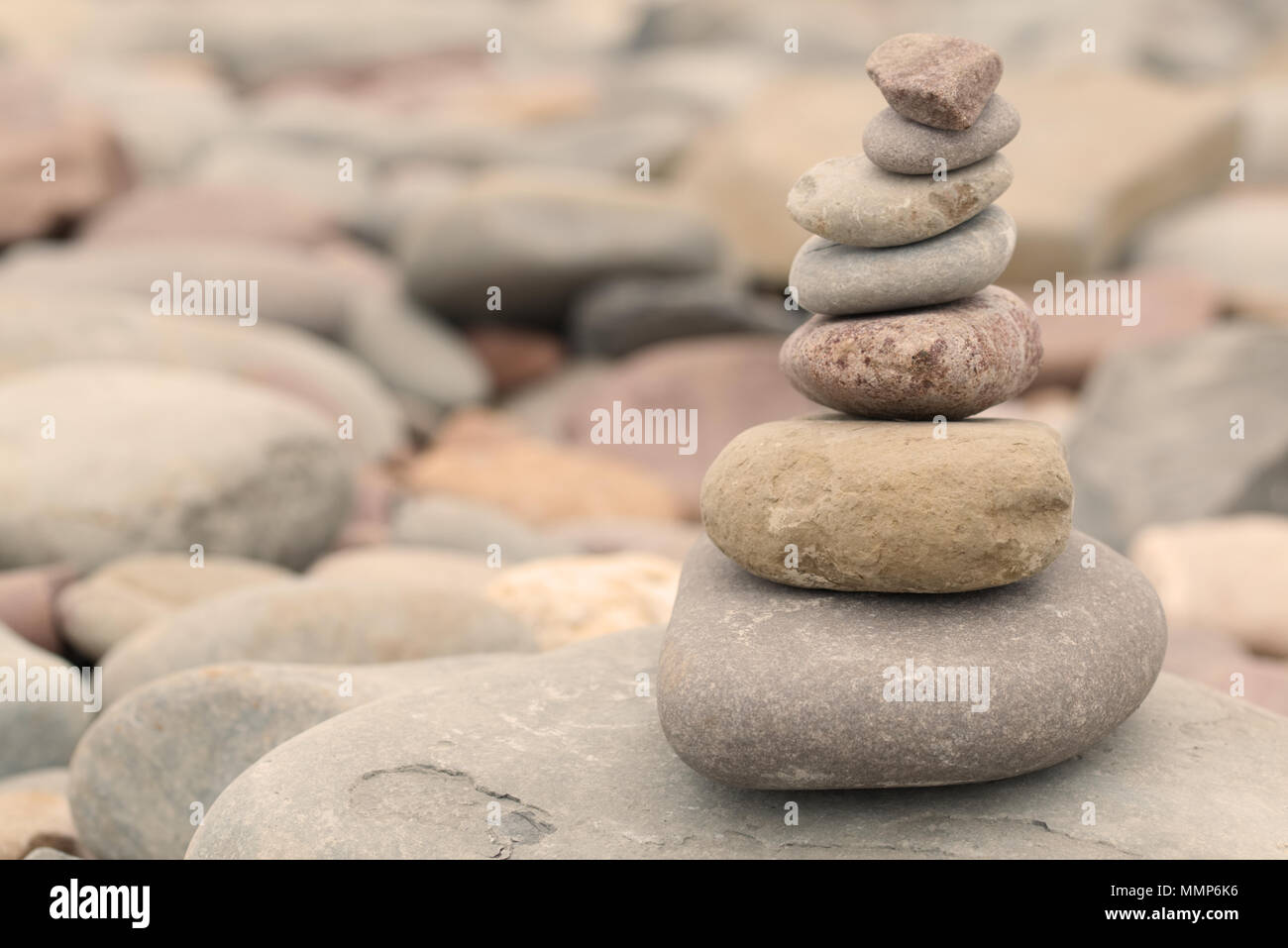 Pile of stones on a pebble beach in warm evening light. Calm peaceful zen concept - Stock Image