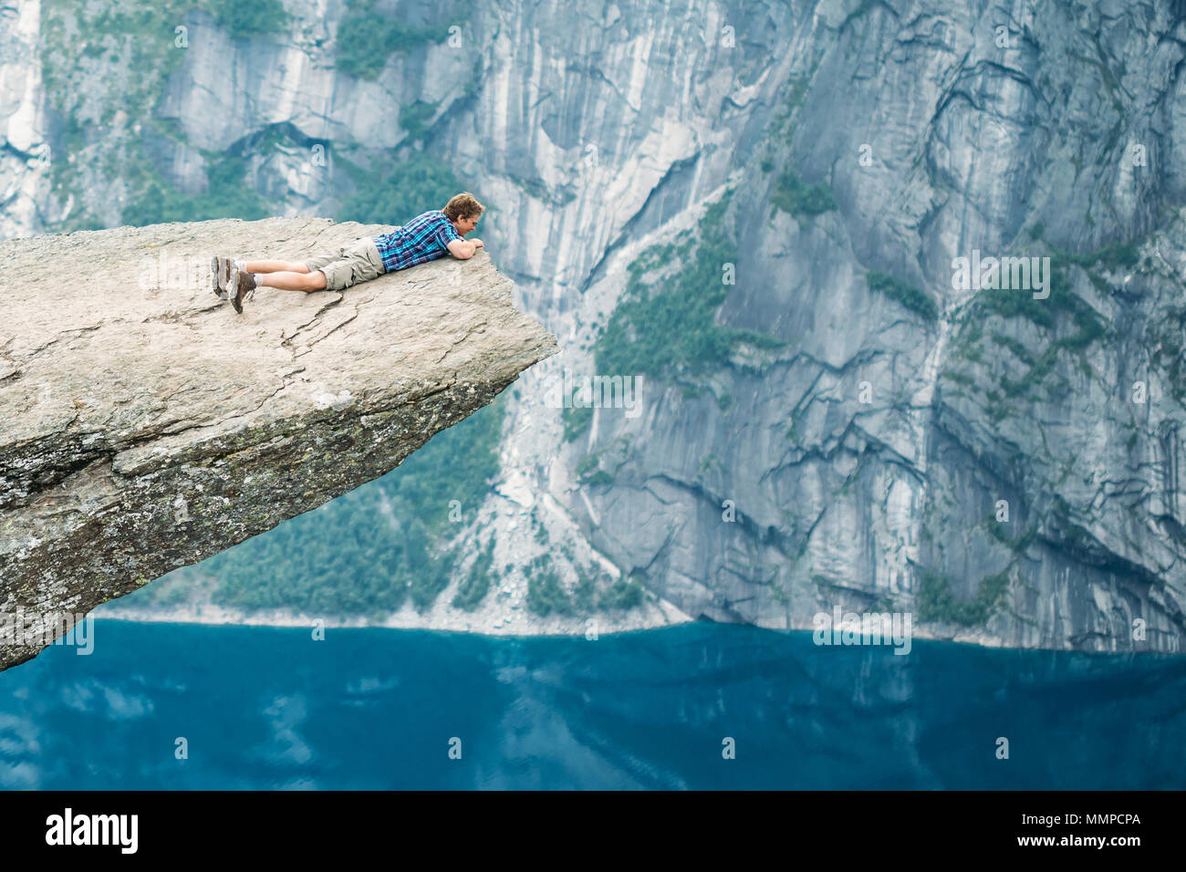 Odda, Norway - August 04, 2014: Young Man On Rock Clings To The Edge Of A Cliff And Looking Down In The Mountains Of Norway. Natural Attractions Of Tr - Stock Image