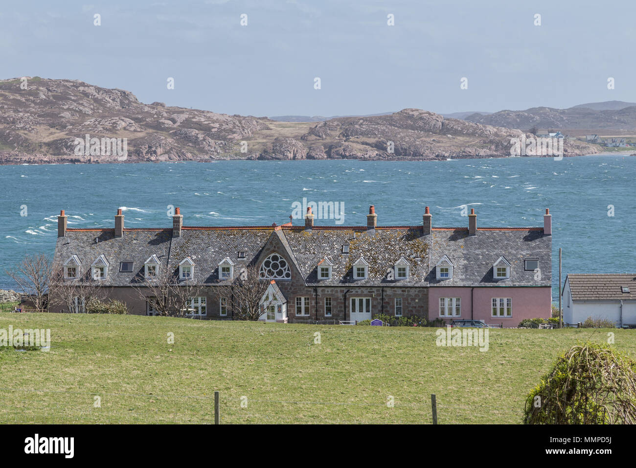 Houses near Iona Abbey on the Isle of Iona, Argyll and Bute on the Inner Hebrides, Scotland, UK with the Isle of Mull and Fionnphort in the background - Stock Image