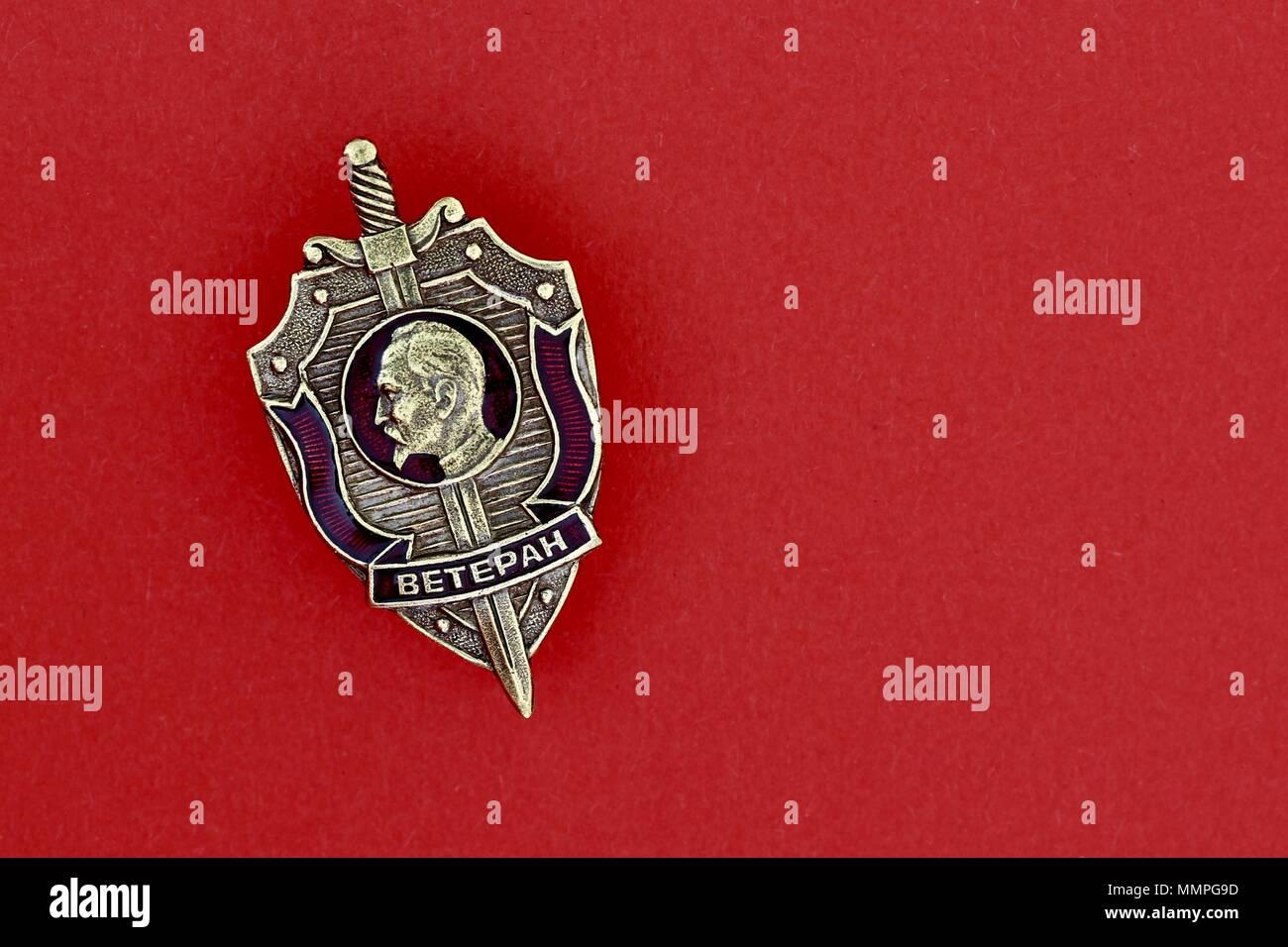 Close up of a Soviet KGB USSR Russian veteran medal. Profile of Felix Dzerzhinsky. Brass metal and enamel badge. Red background. - Stock Image