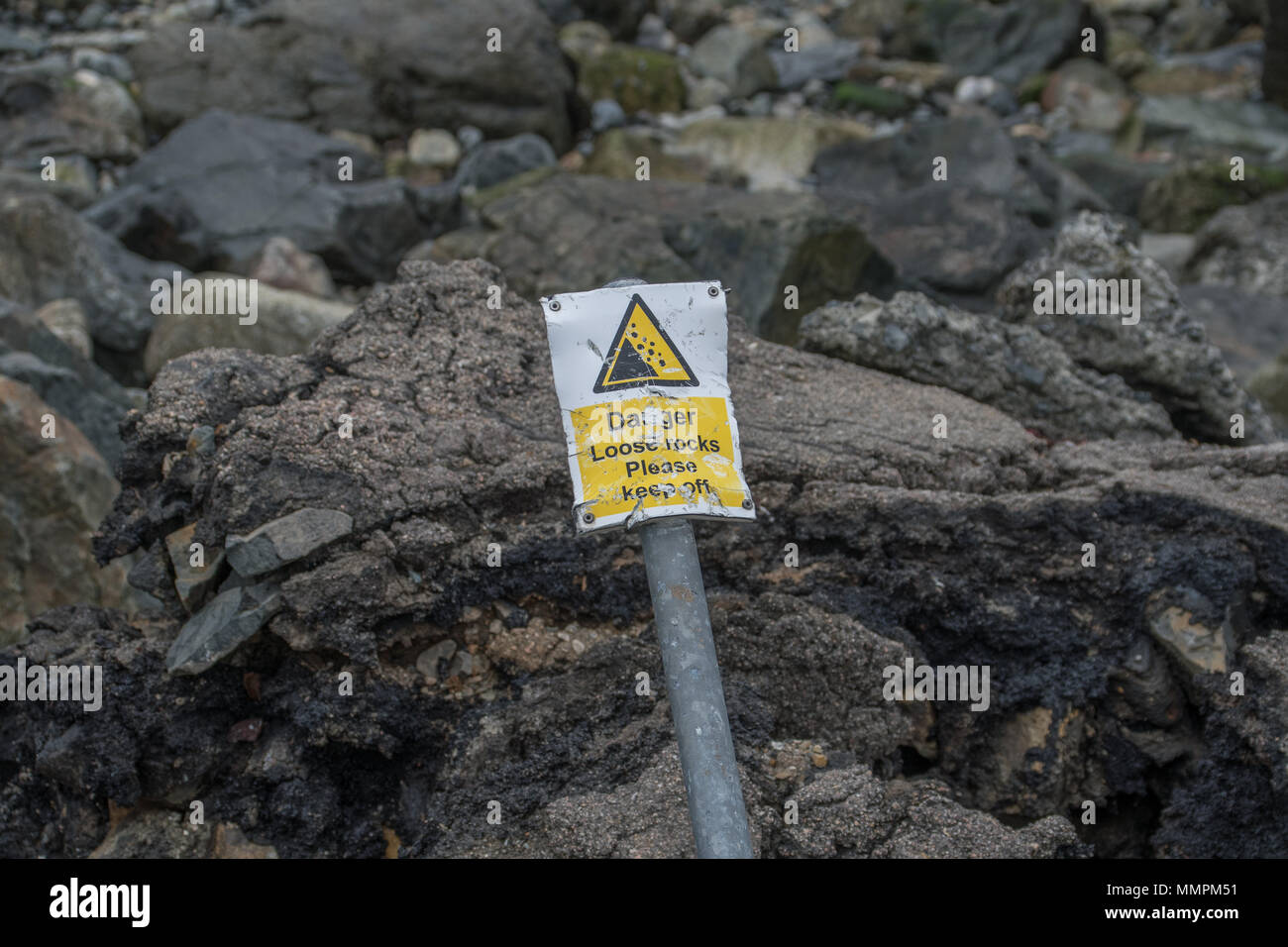 Danger loose rocks sign which has been bent and is falling over against some loose rocks on the coast at Newlyn in Cornwall - Stock Image
