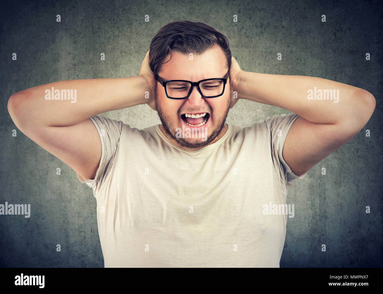 Stressed bearded man in glasses covering ears having hysteria and nervous breakdown. - Stock Image