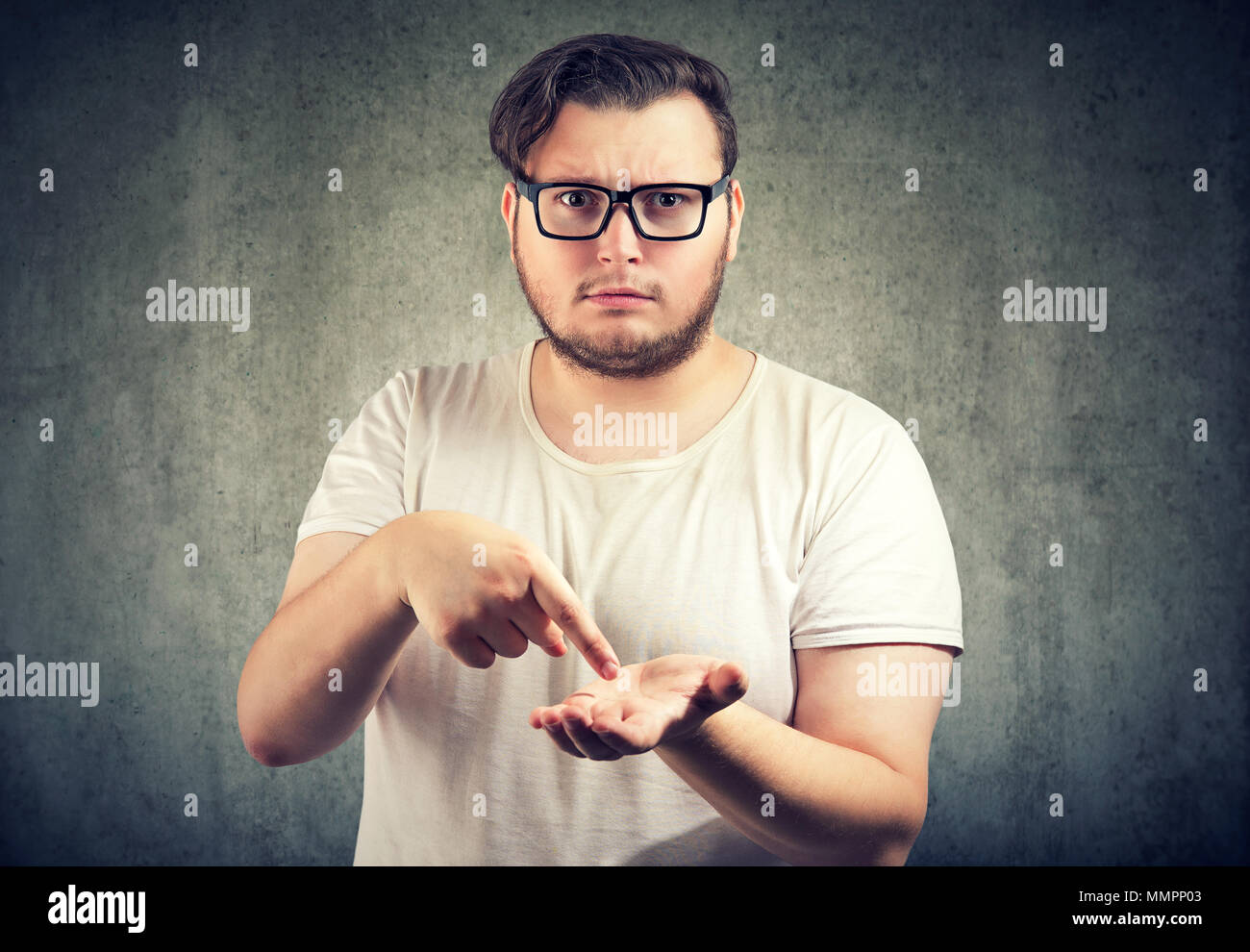 Young serious chubby man asking for more money to pay back debt - Stock Image