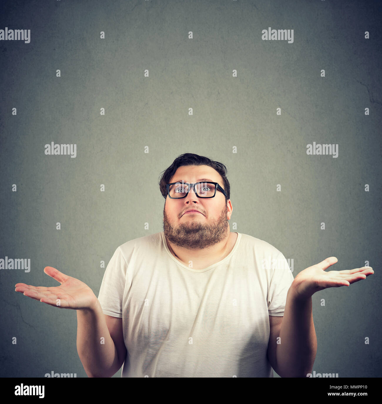 Young bearded chubby man looking super puzzled and shrugging shoulders in question holding hands apart. - Stock Image