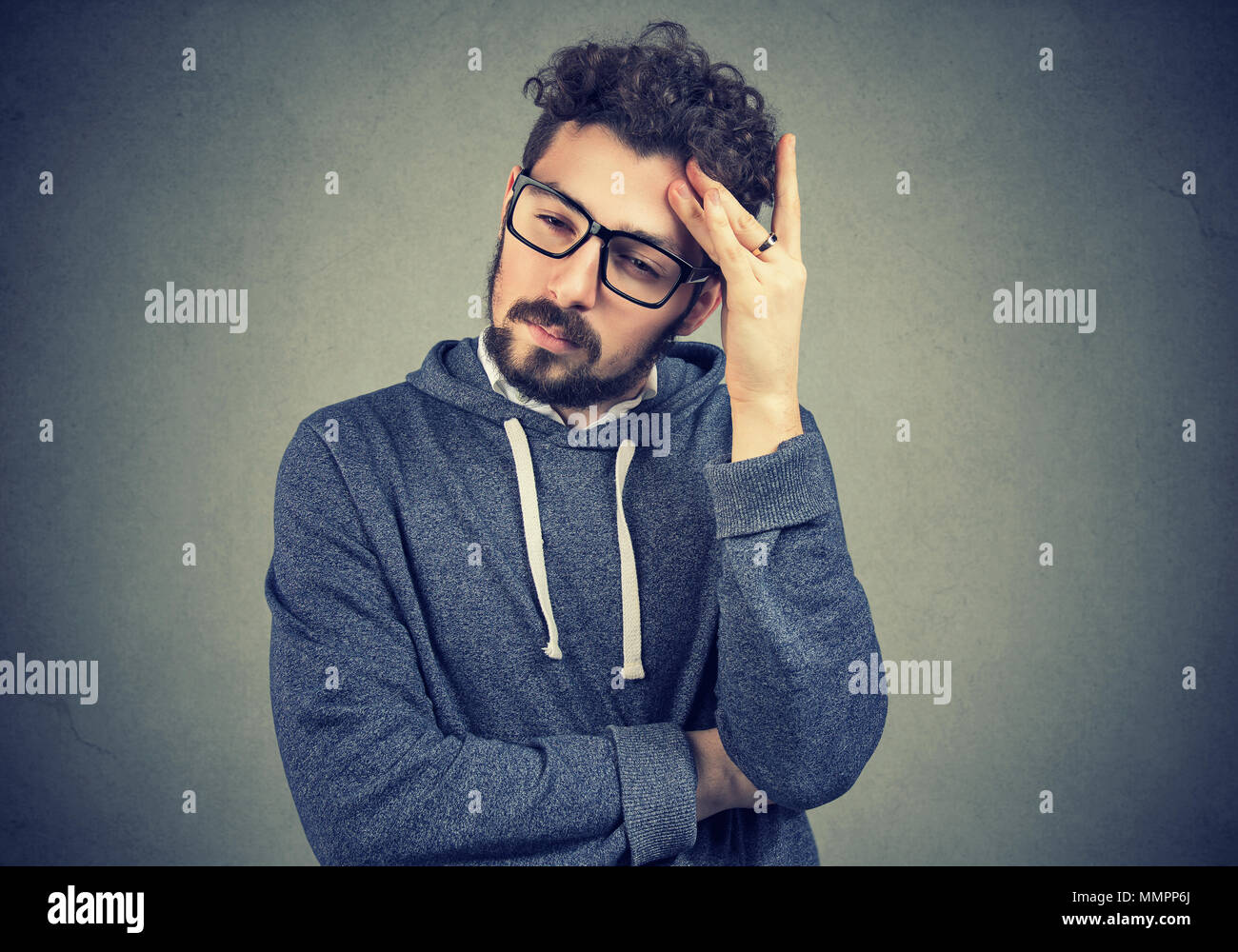 Sad preoccupied man looking down standing on gray background - Stock Image
