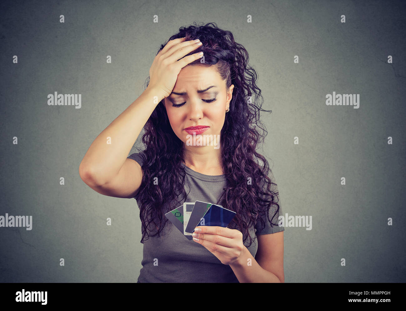 Confused stressed woman looking at too many credit cards - Stock Image