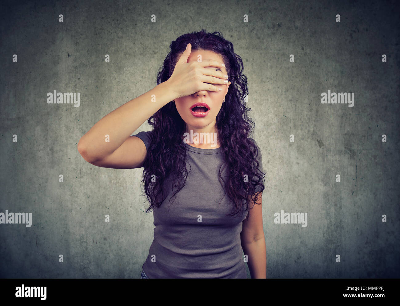 Regretful young woman covering her eyes - Stock Image