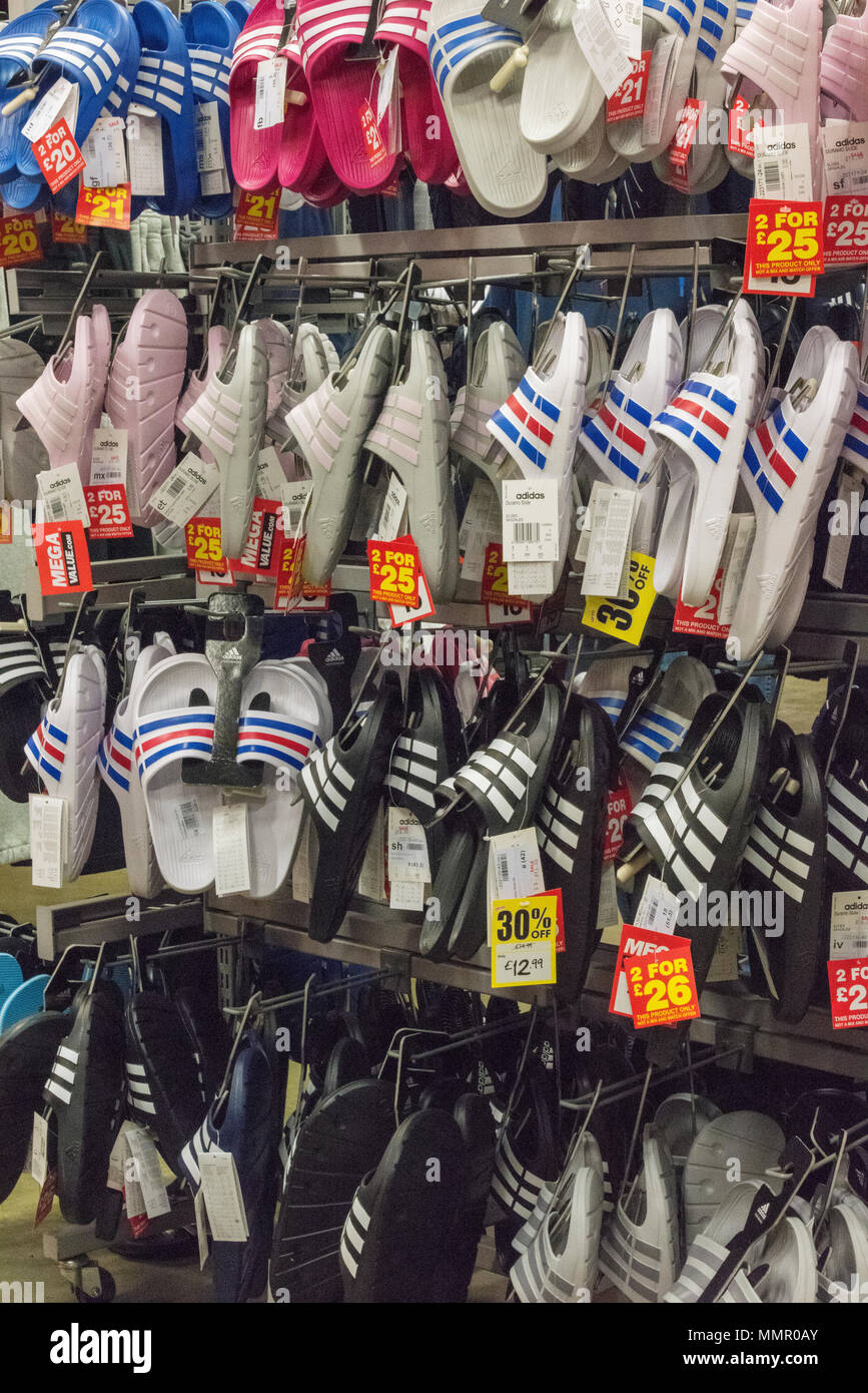 a selection of training shoes and flip flop shoes on sale at a major sports equipment and clothing retailer on the high street. - Stock Image