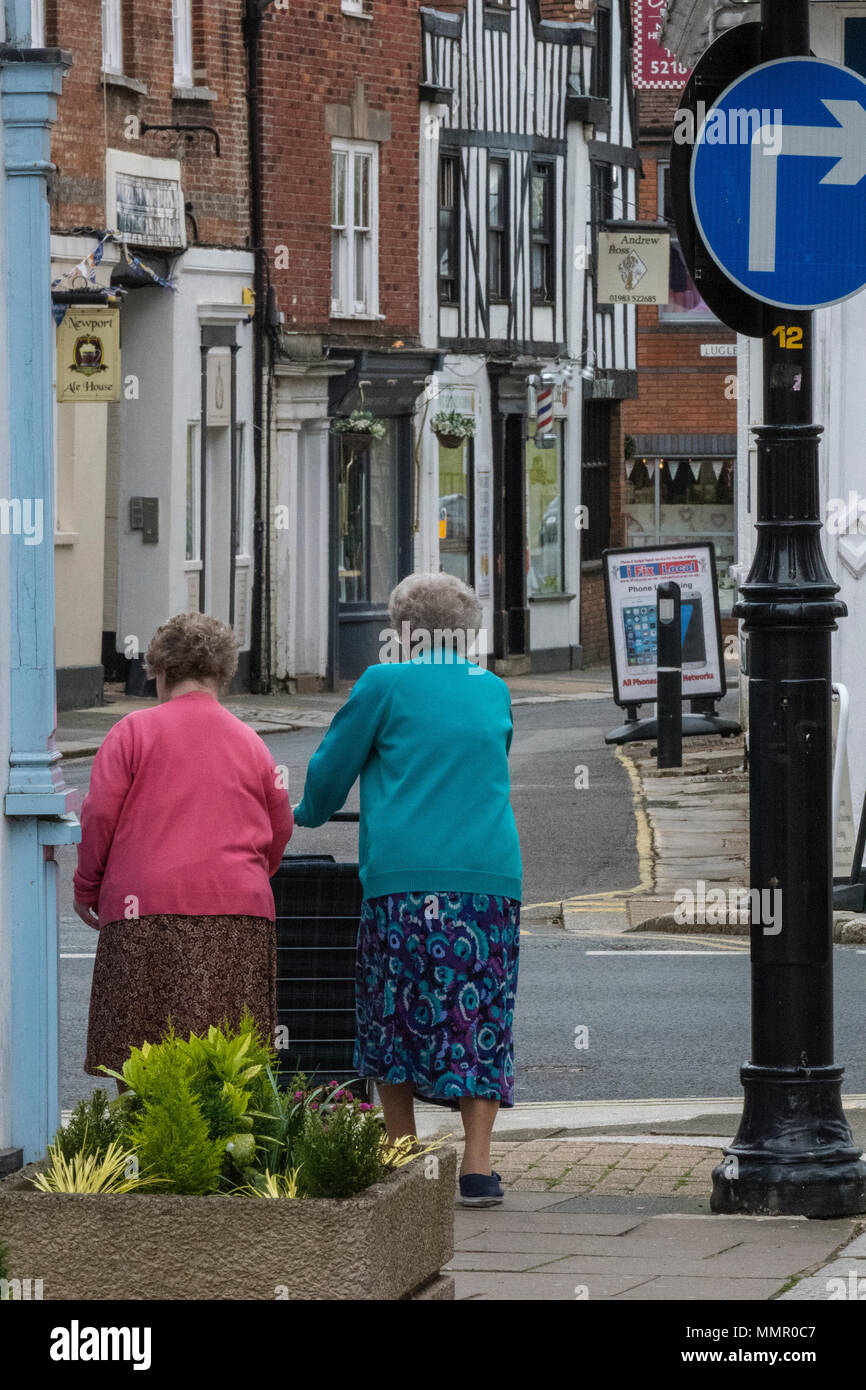 two elderly ladies walking in a town centre shopping together pushing a trolley. - Stock Image