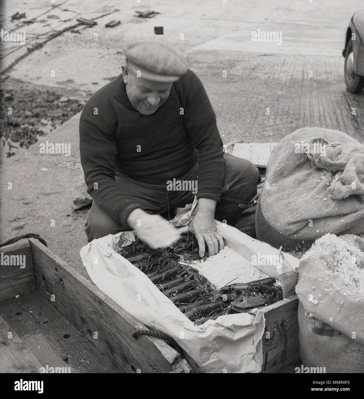 1950s, historical, a fisherman carefully putting his catch