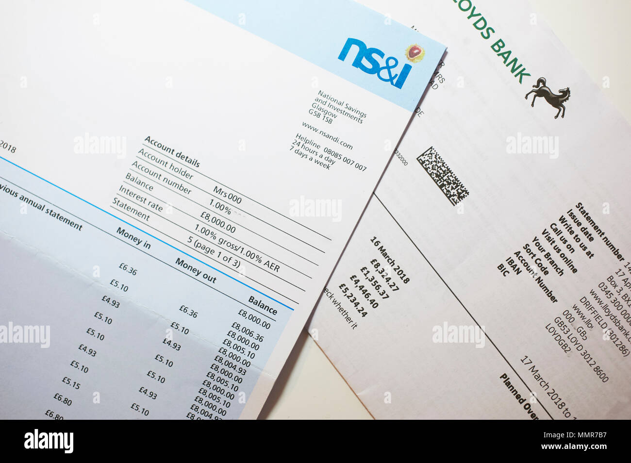 NS&I and Lloyds Bank Statements showing investments on a wooden desk top. - Stock Image