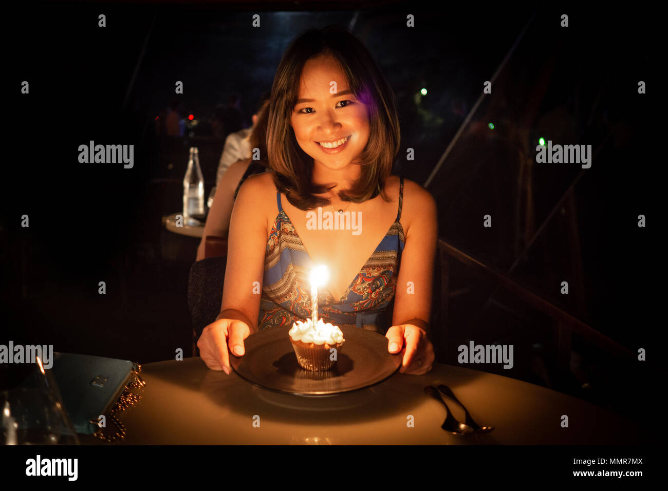 Young woman celebrating her birthday at a dinner in a nice restaurant - Stock Image