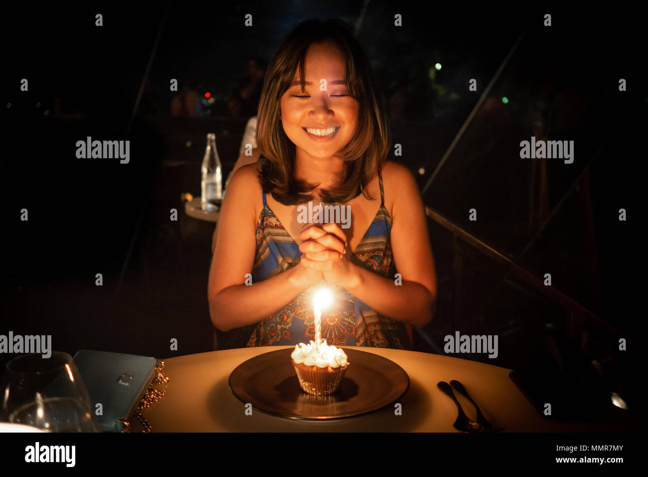 Young woman celebrating her birthday and making a wish at a dinner in a nice restaurant - Stock Image