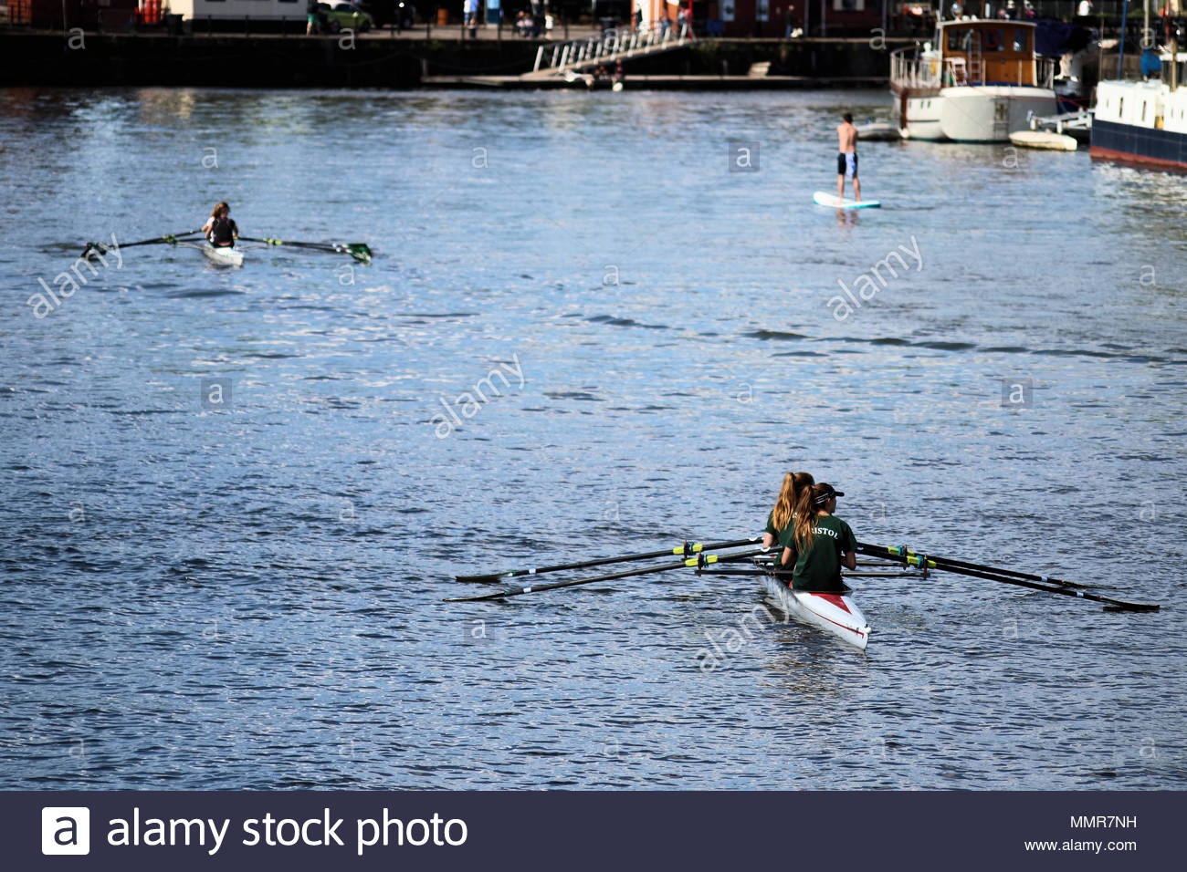 Two sets of Rowers in Bristols Floating Harbour, Bristol City Centre, UK - Stock Image