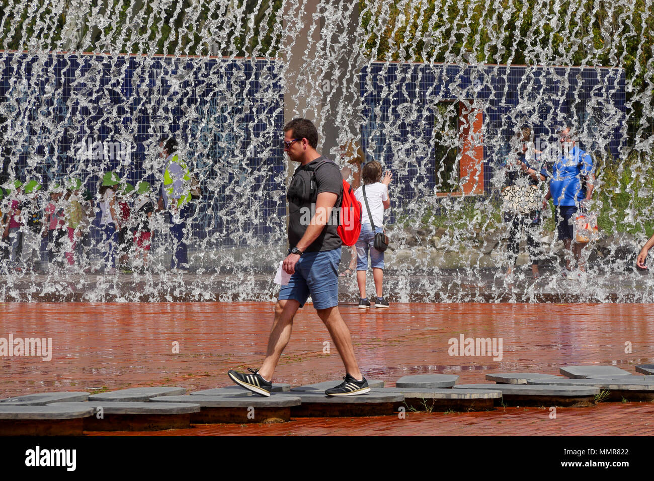 Tourist walking in front of a water curtain, in Park of the Nations district. Lisbon, Portugal - Stock Image