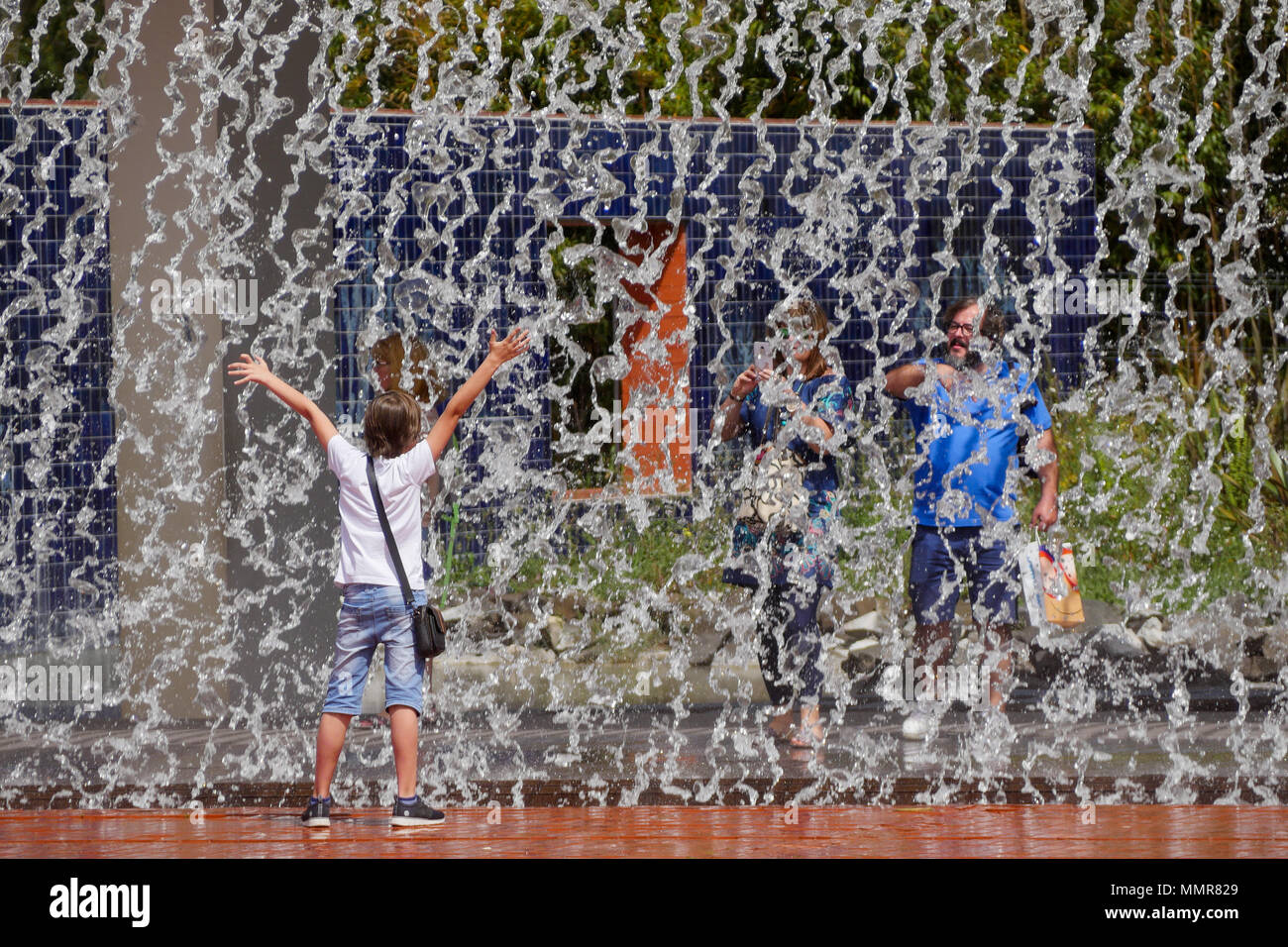 Young boy playing in front of a water curtain, in Park of the Nations district. Lisbon, Portugal - Stock Image