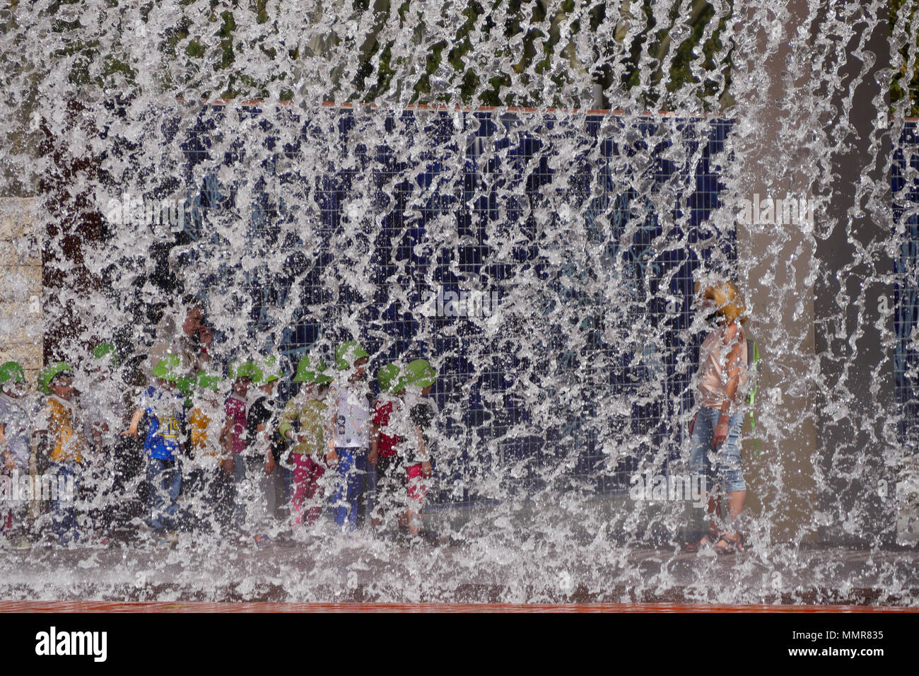 People standing behind a water curtain, in Park of the Nations district, Lisbon, Portugal - Stock Image
