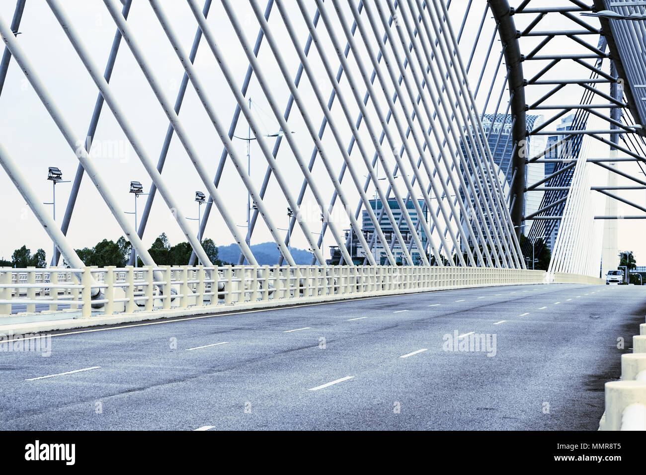 Details of modern architecture - an empty asphalt road on a large bridge in Cyberjaya, Malaysia. Toned in cool colors, cyan. - Stock Image