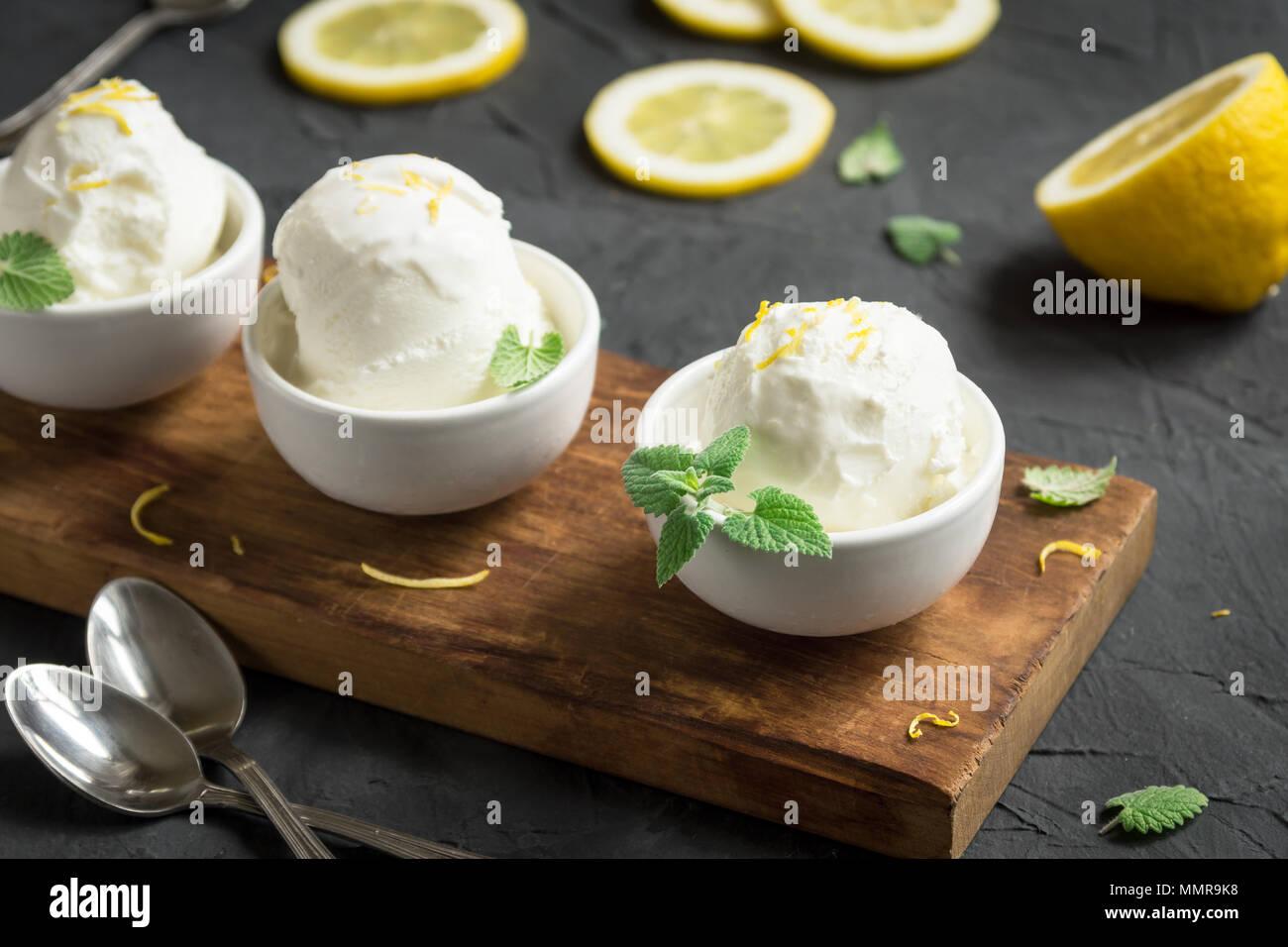 Lemon Ice Cream in bowl. Homemade citrus lemon ice cream (gelato) with mint close up. - Stock Image