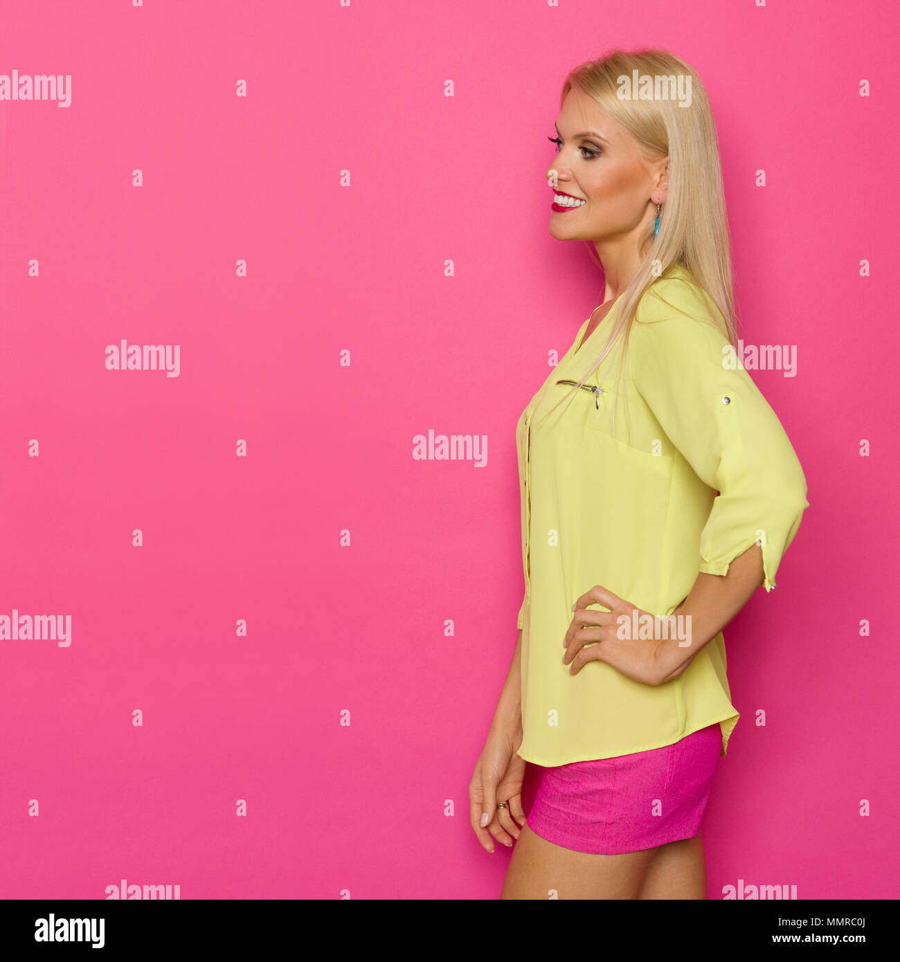 586b6ec5d6775 Beautiful blond woman in yellow shirt and pink shorts is holding hands on  hip