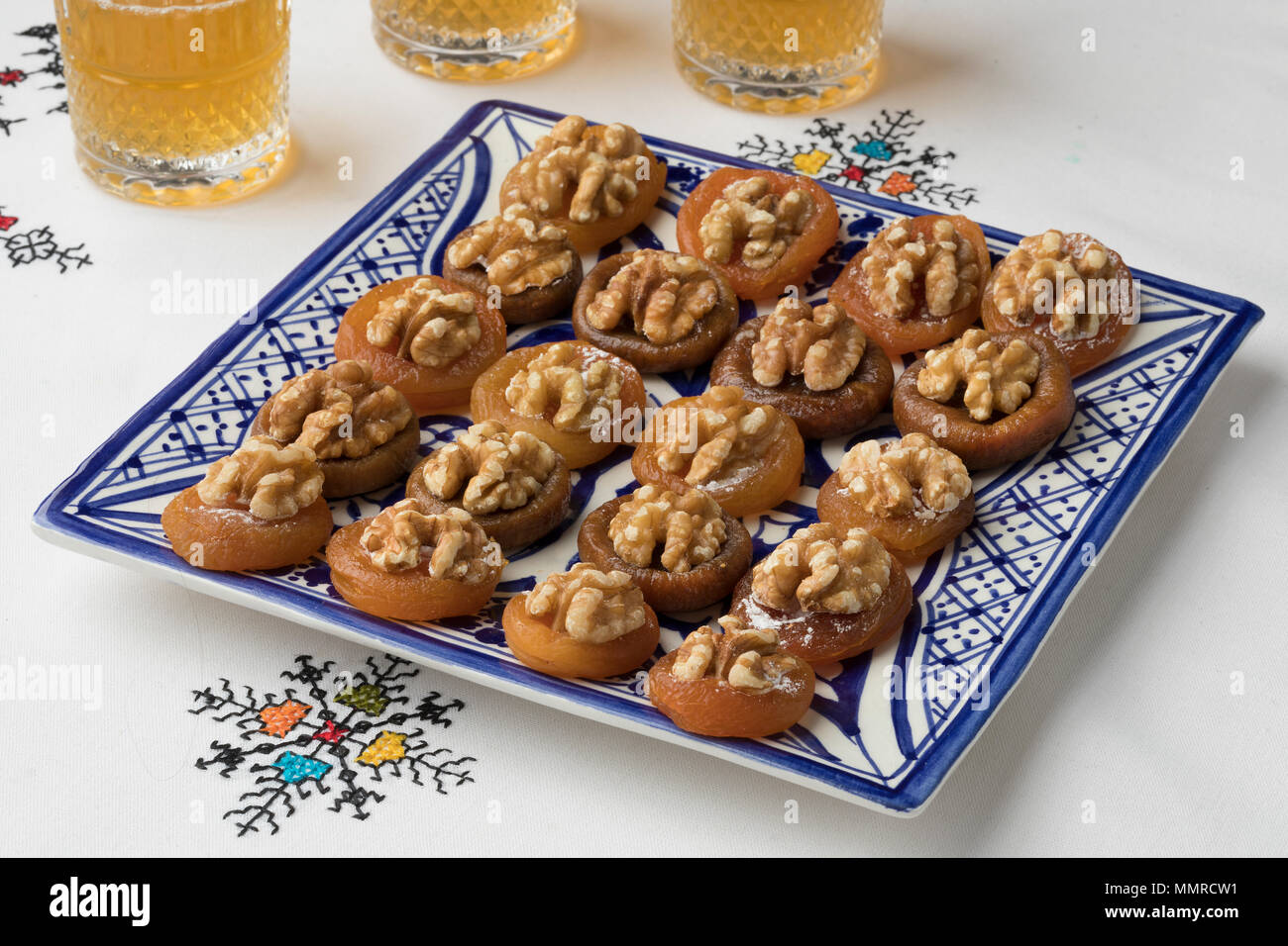 Dish with Moroccan dried apricots decorated with a walnuts and tea on a embroidered tablecloth - Stock Image