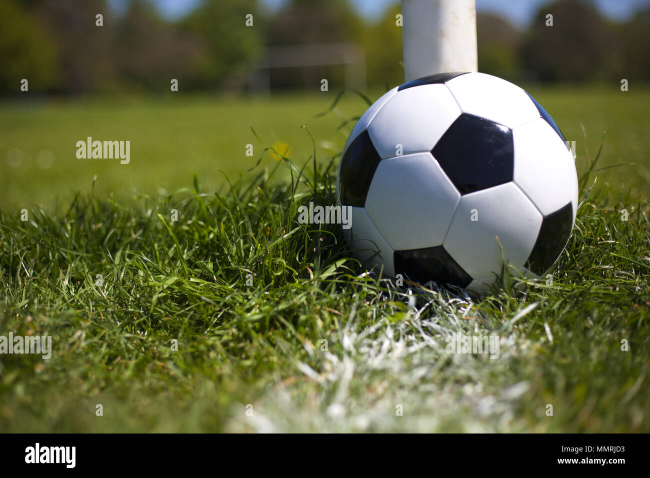 A black and white leather football near the post and white line - Stock Image