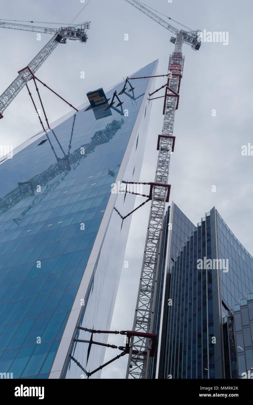 Skyscraper view with with cranes to the side of building. - Stock Image