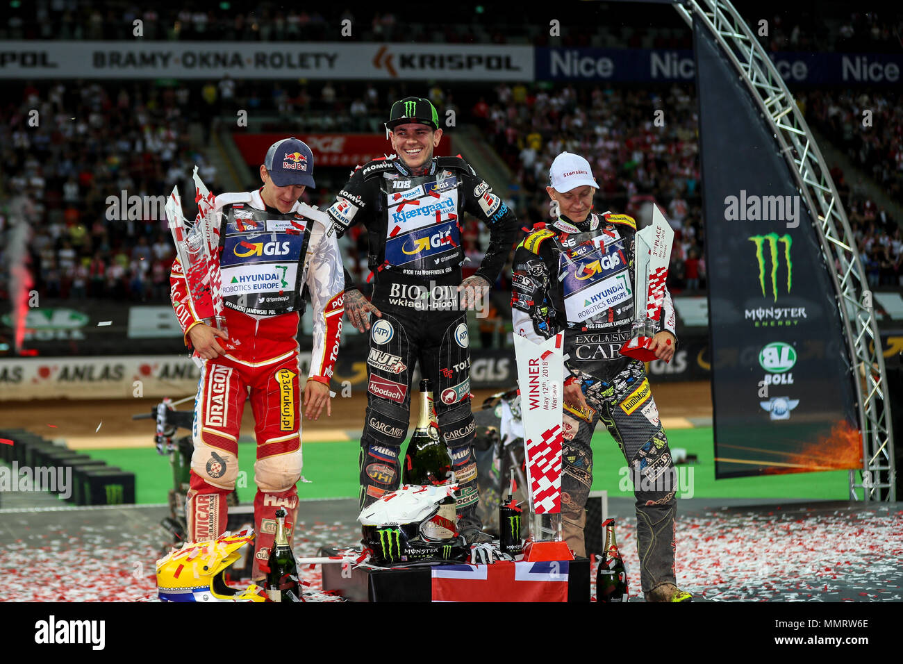 12th May, PGE National Stadium, Warsaw, Poland; Boll Warsaw FIM Speedway Grand Prix of Poland; Tai Woffinden laughs with the organisers as he could not get the champagne open whilst he celebrates winning the Warsaw FIM Speedway Grand Prix - Stock Image