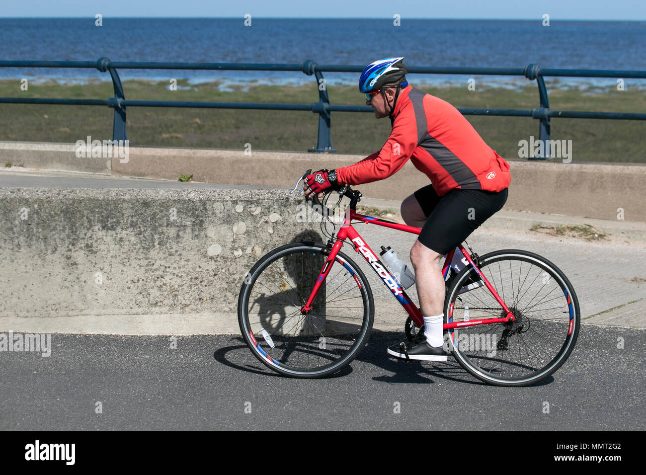 Southport, Merseyside, UK 13/05/2018. UK Weather. Bright colours on a bright sunny day at the coast, as temperatures in the North West are expected to rise.  Residents of the resort take light morning exercise on the seafront promenade at the start of the day. Credit: MediaWorldImages/AlamyLiveNews Stock Photo